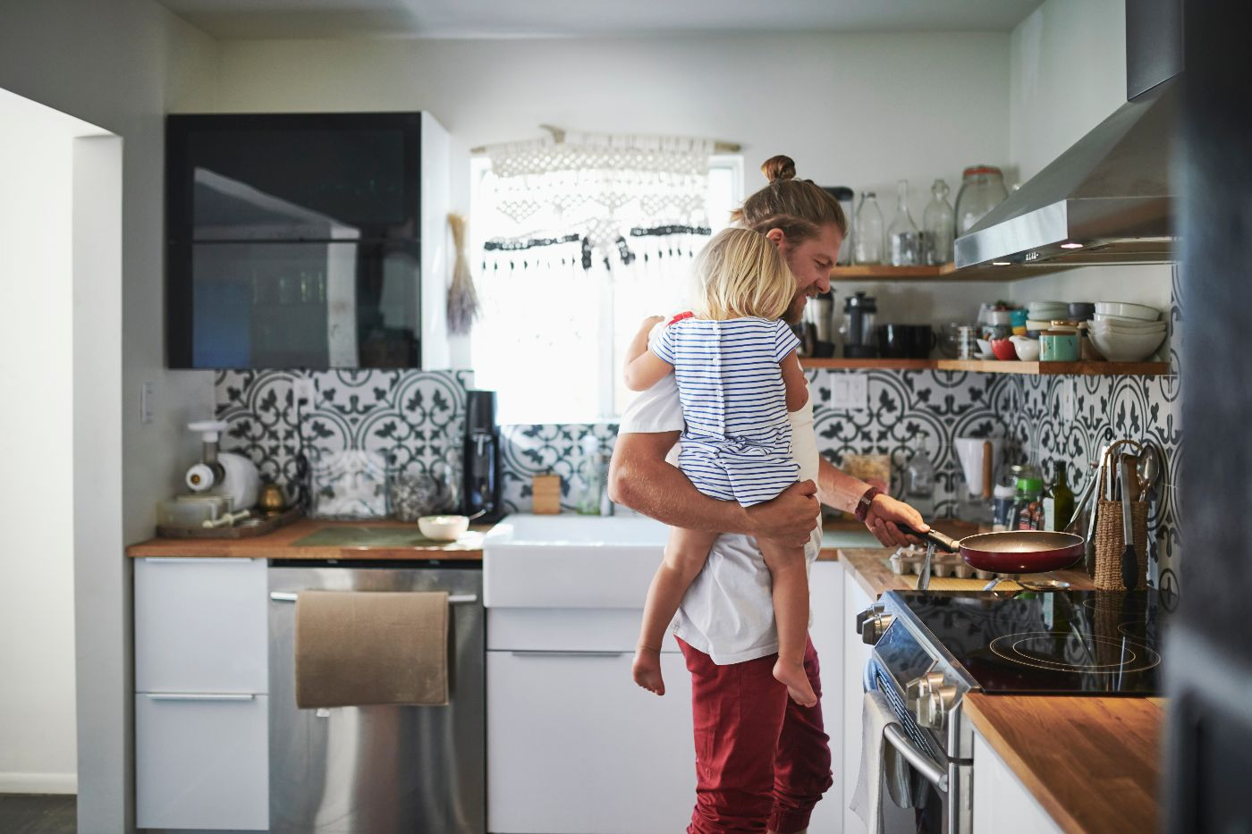Mid adult father carrying daughter while cooking food in kitchen