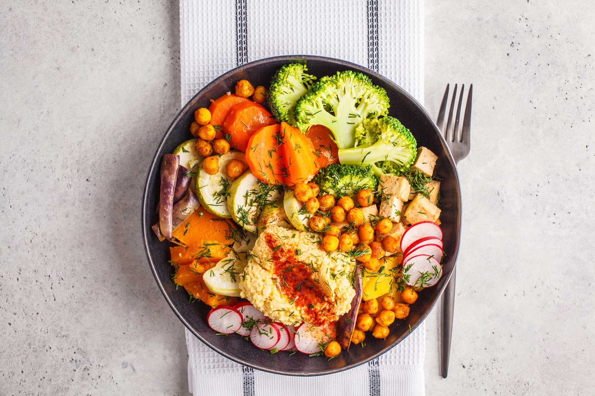 Grain bowl with hummus, roasted chickpeas, radishes, broccoli, sweet potato, carrots, and tofu