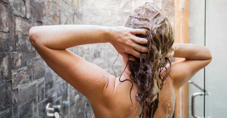 Woman washing head in shower