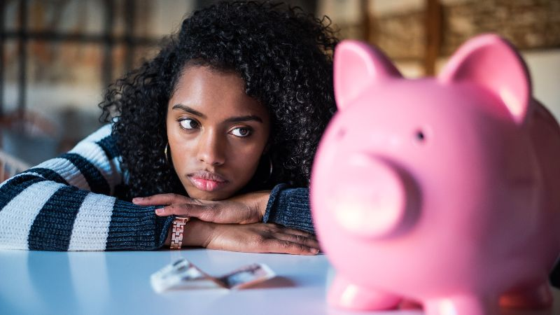 Sad frustrated black woman with piggy bank