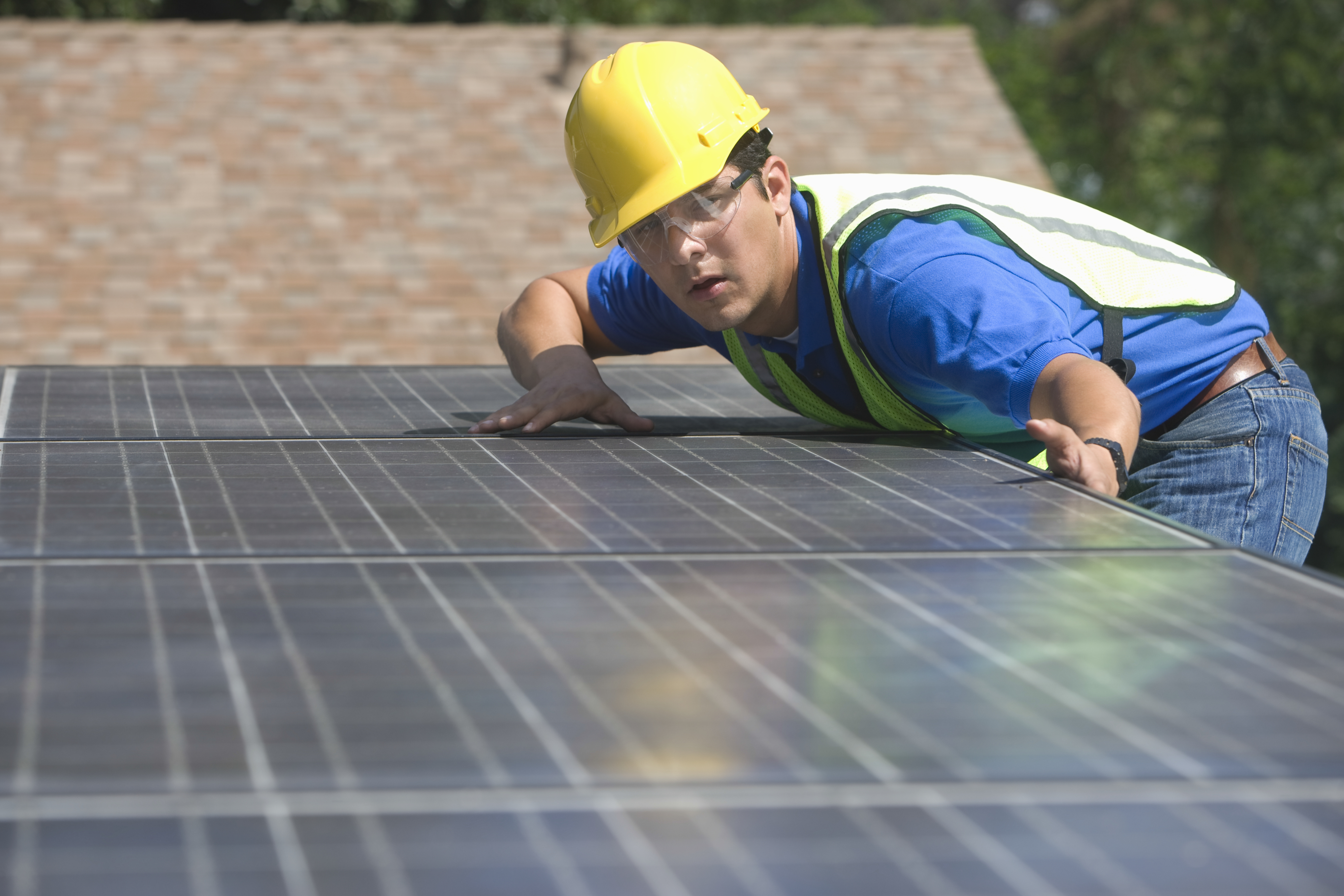 Worker Installing Solar Panels On Rooftop