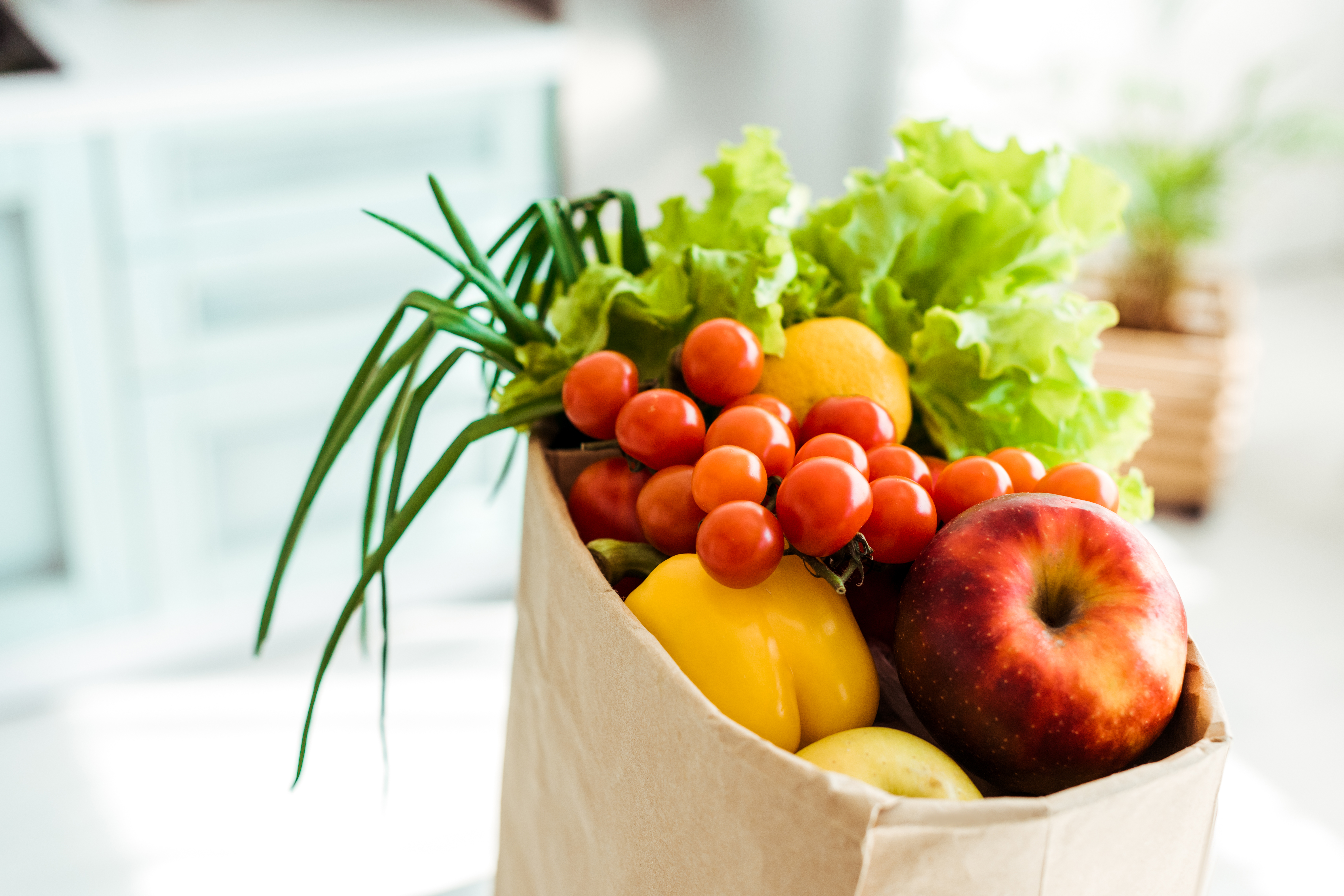 fresh whole and ripe fruits and vegetables in paper bag