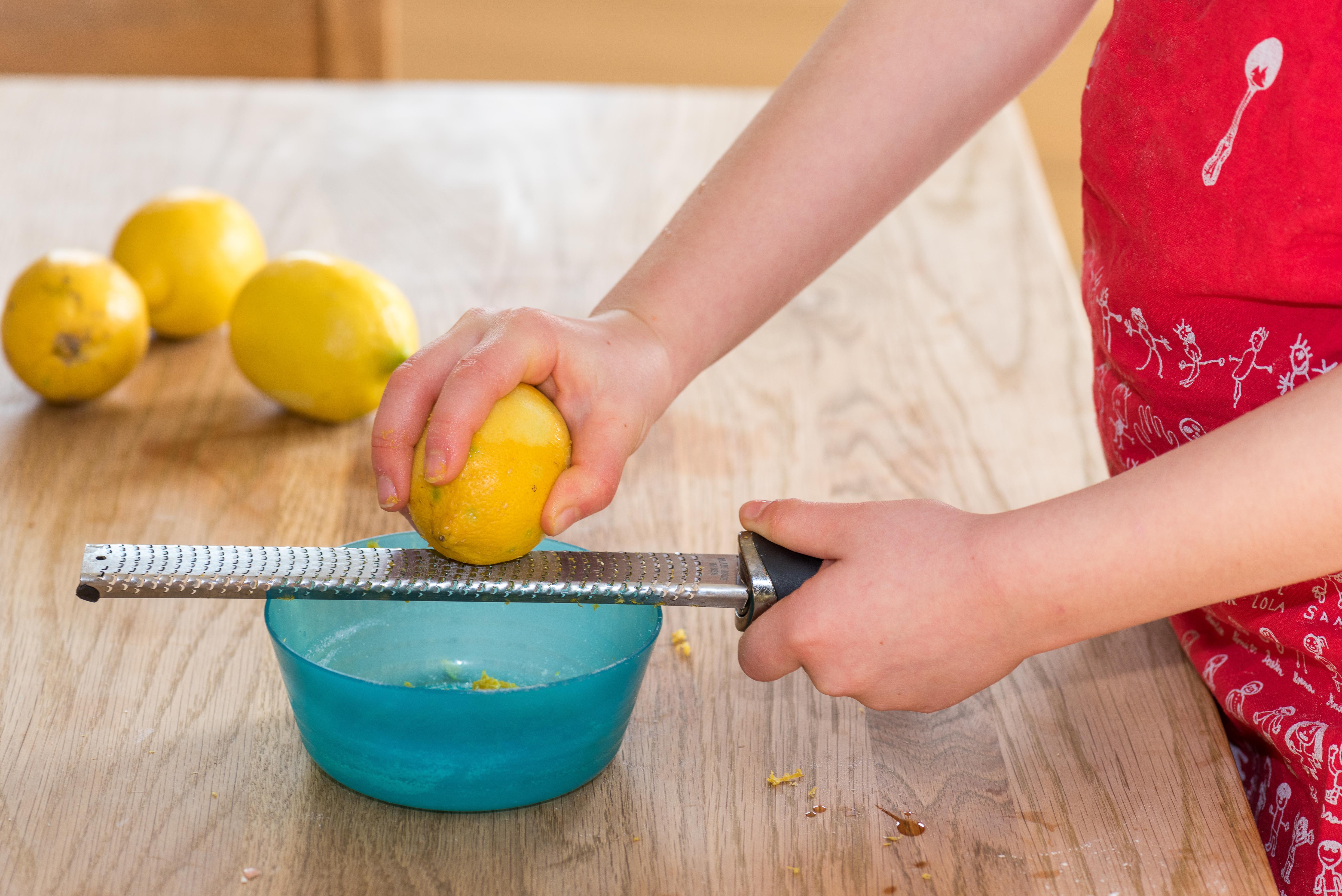 Little girl grating zest of organic lemon on kitchen table