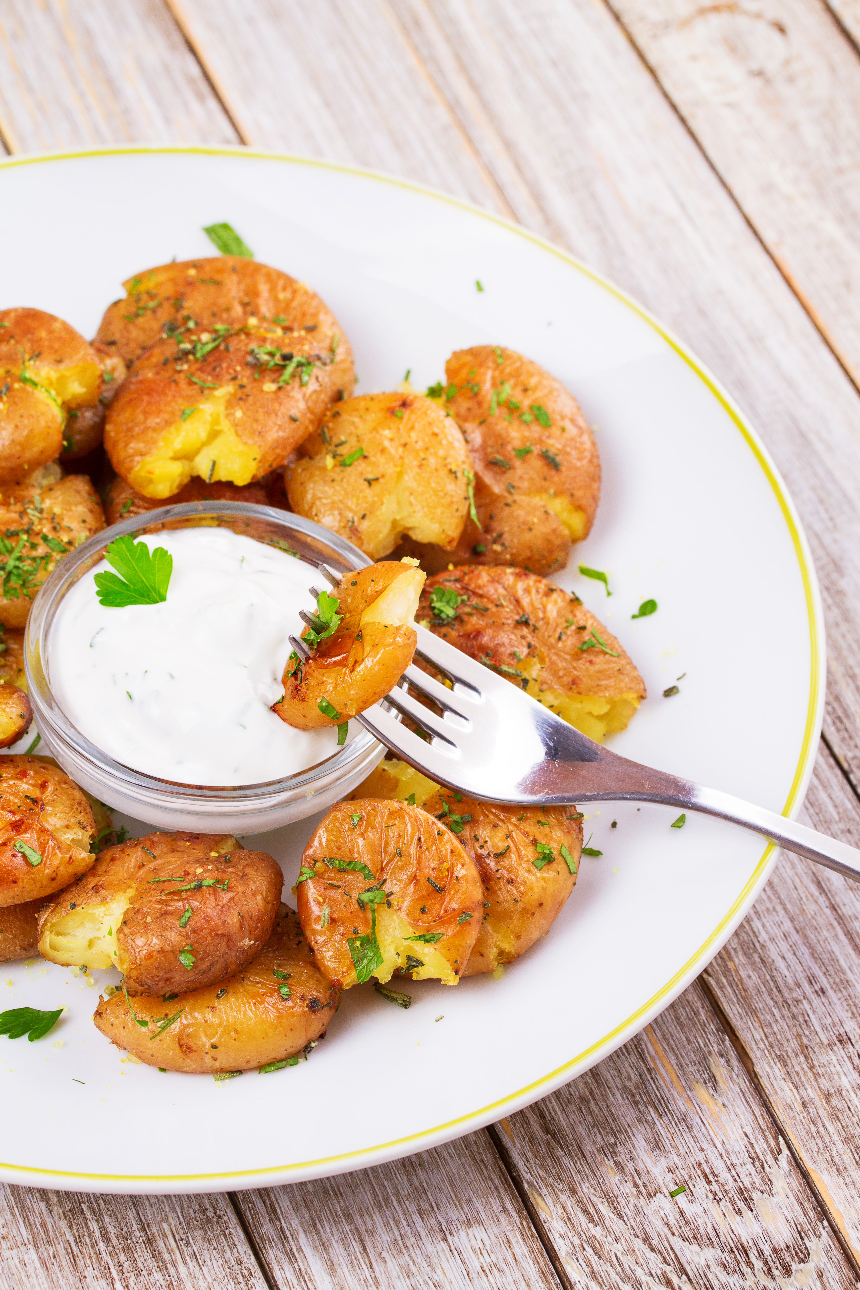 Smashed Potatoes with parsley, dried rosemary, lemon zest and yogurt sauce