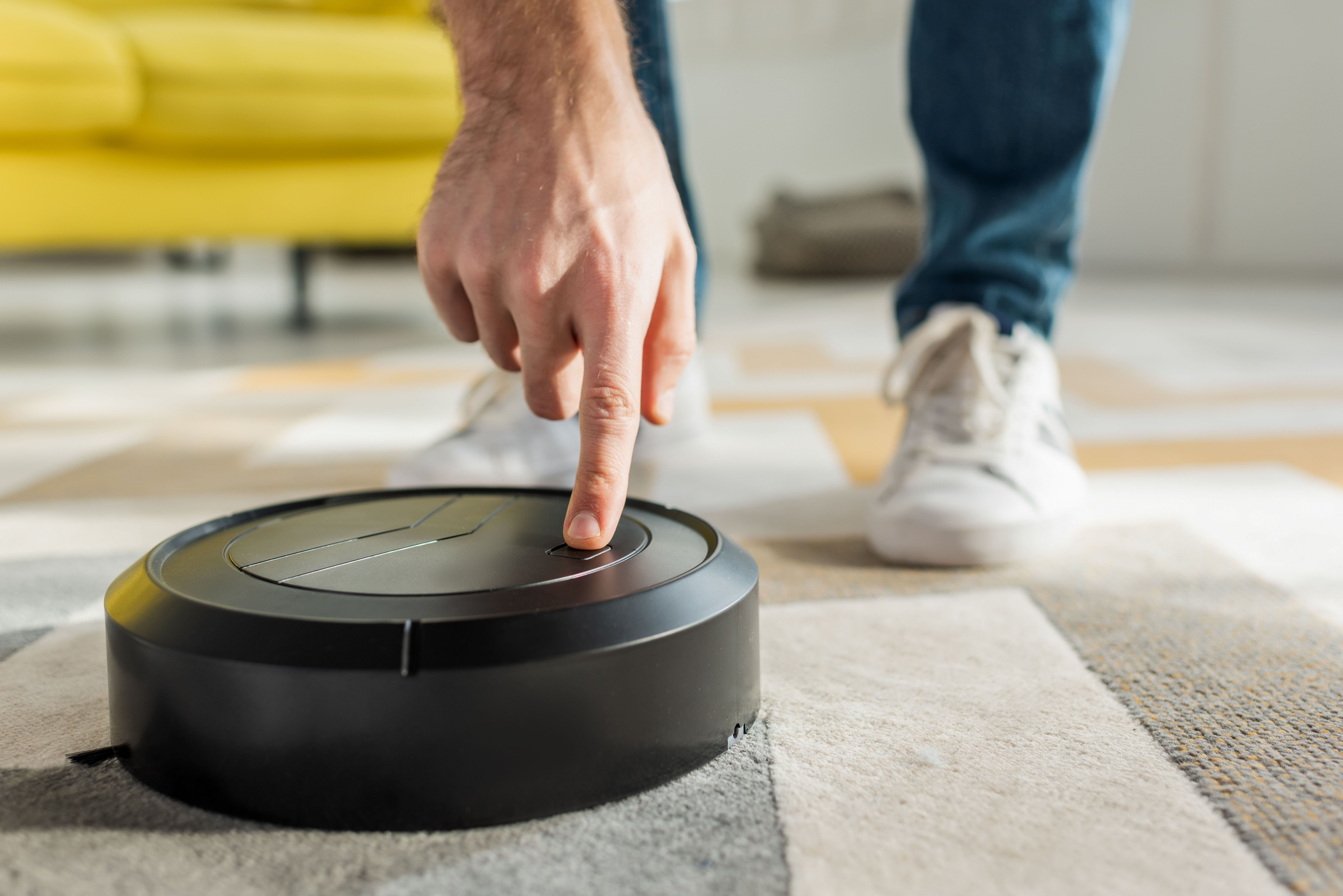 cropped view of man pointing with finger at robotic vacuum cleaner in living room