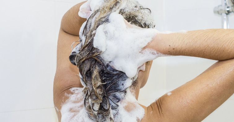 Lovely woman lathering her hair with shampoo in the shower