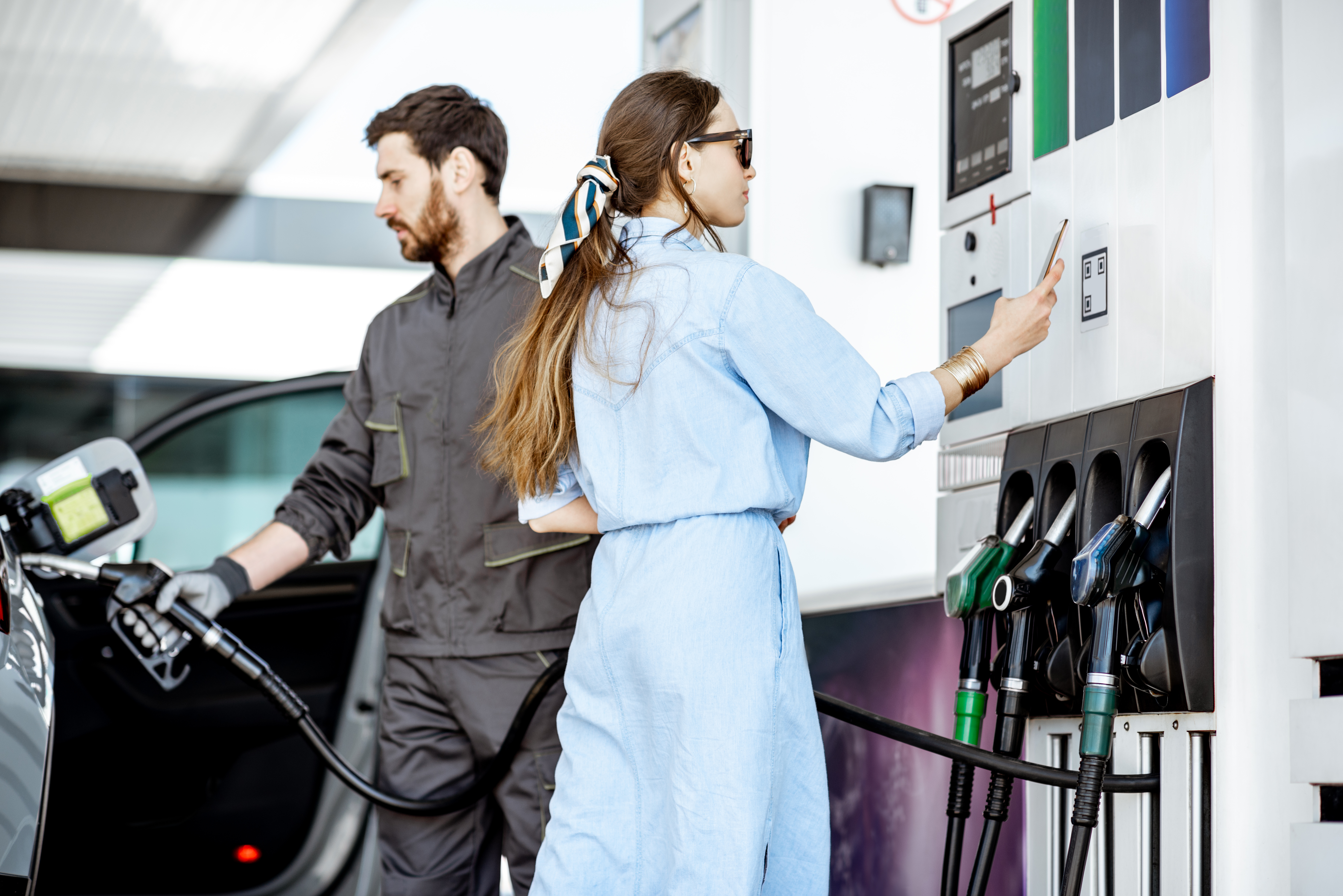 Woman paying with phone at the gas station