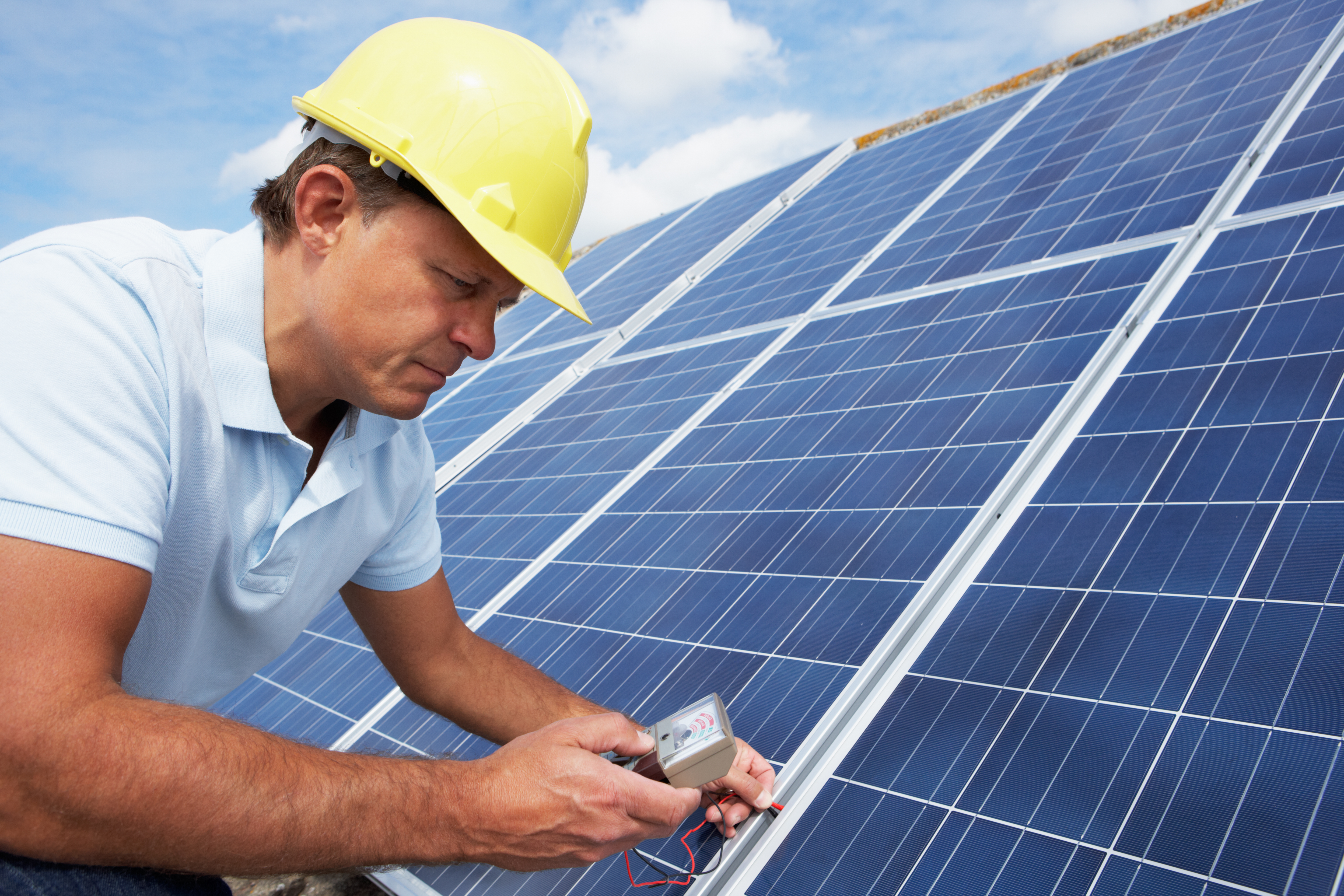 Man wearing hard hat checking roof solar panels