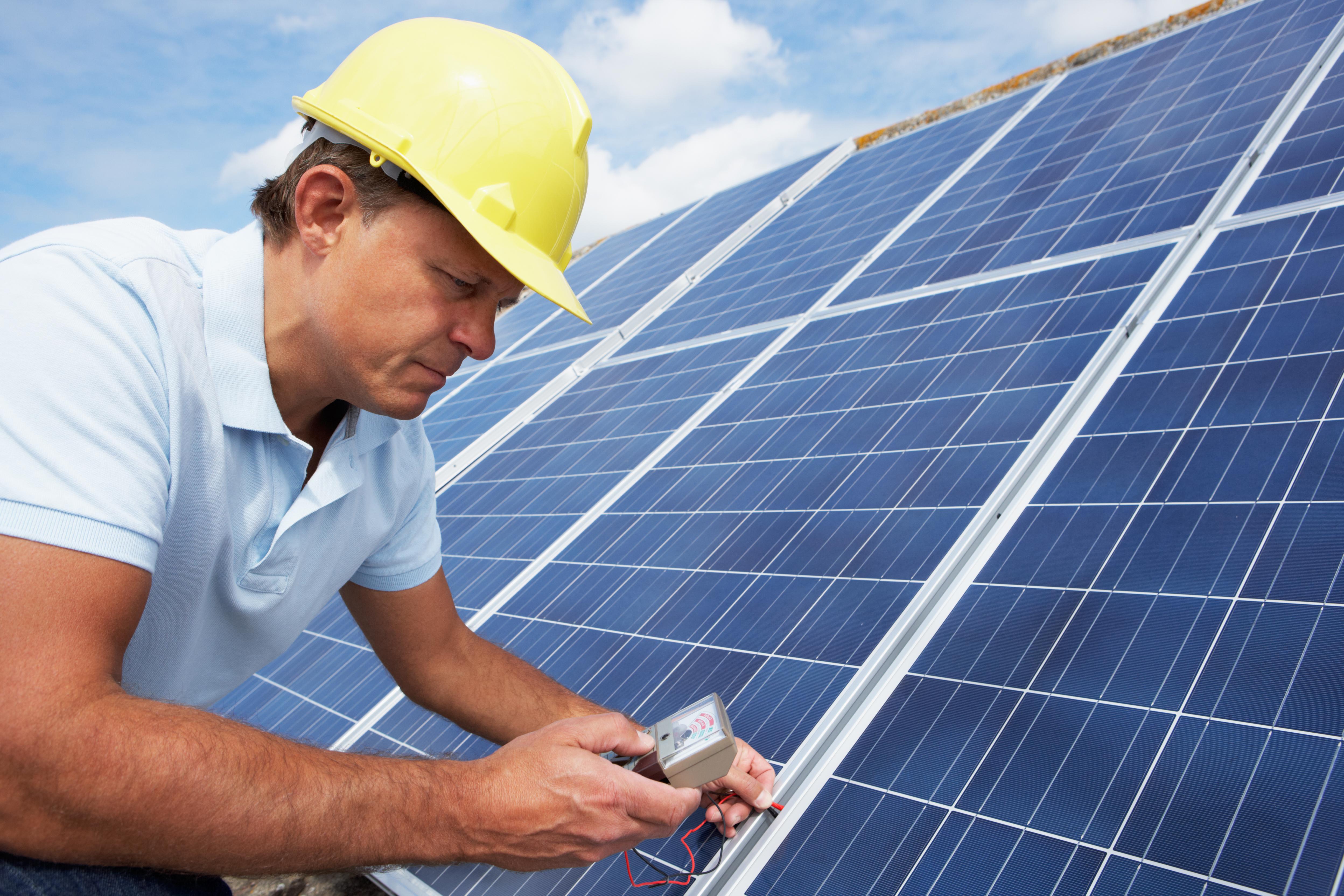 Man wearing hard hat checking roof solar panels