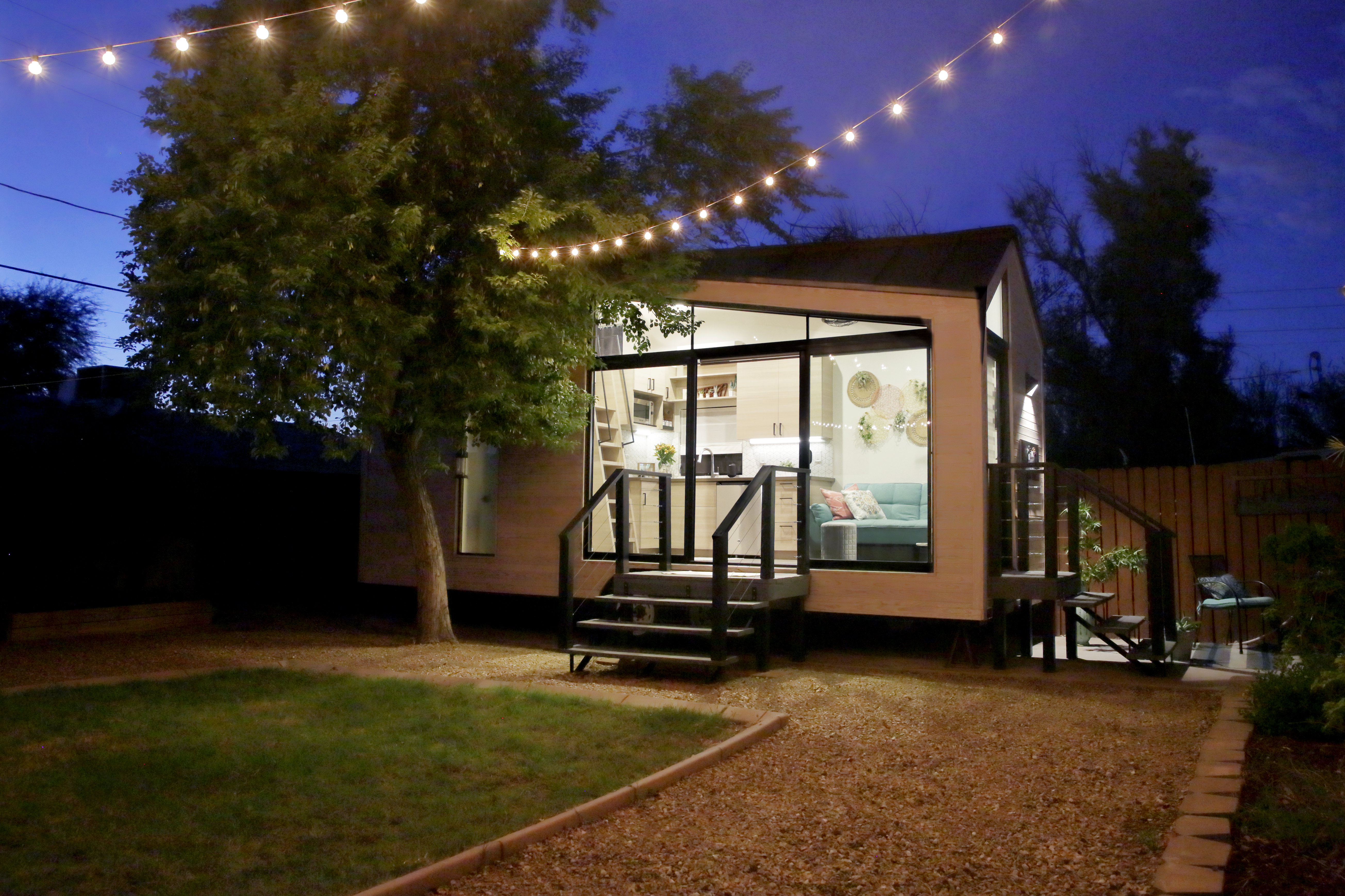 A tiny house with large glass windows, sits in the backyard at night, surrounded by trees and party lights.