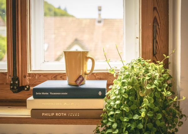 window with cup of tea on stack of books