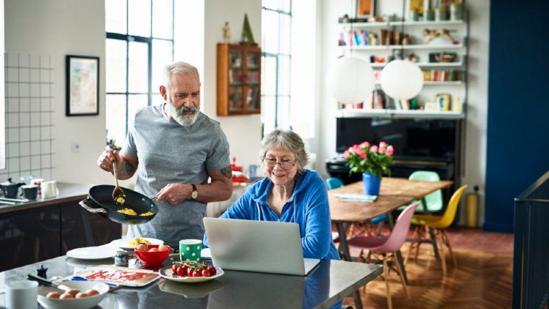 Senior woman using laptop and smiling as man serves breakfast