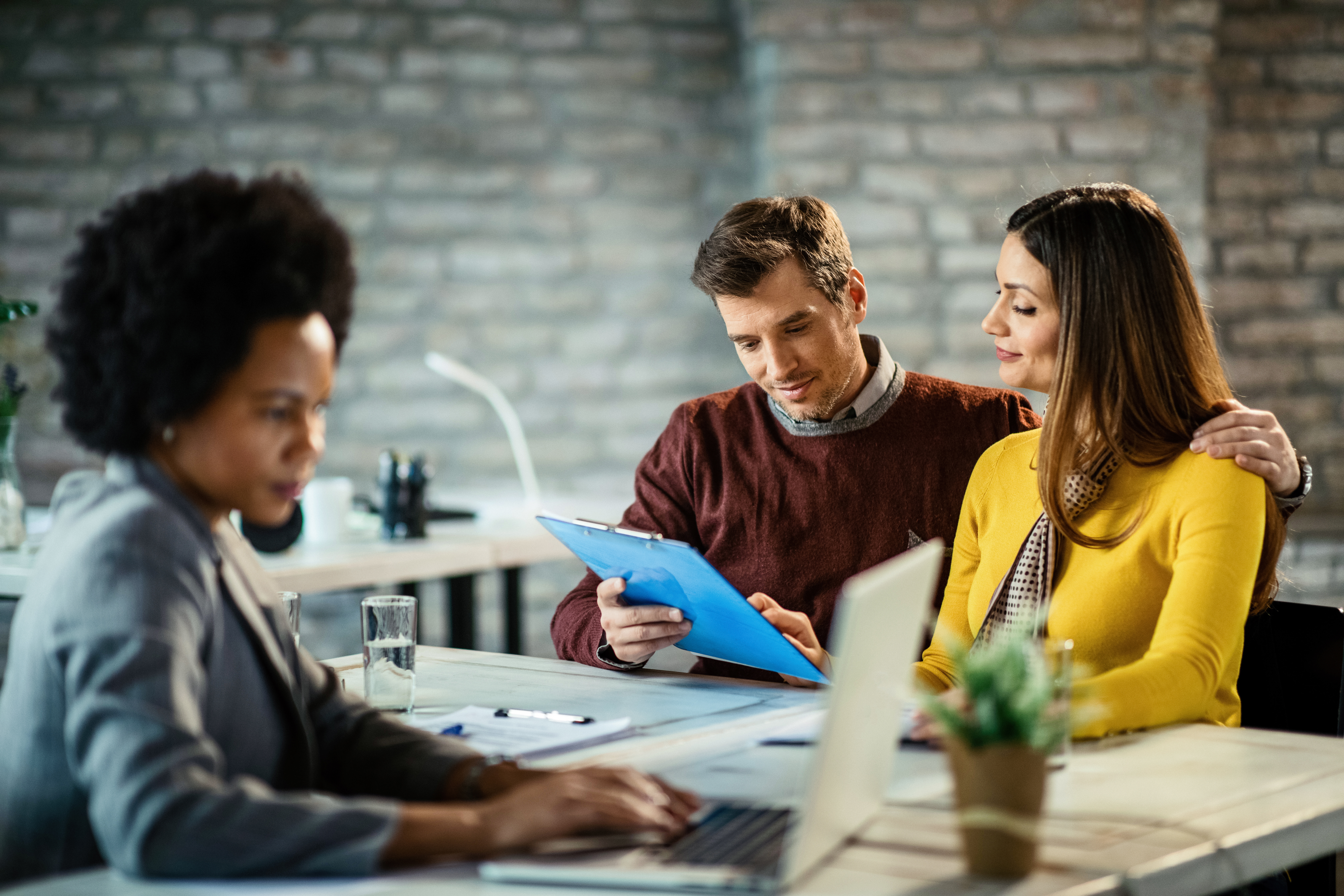 Smiling couple analyzing their financial reports on a meeting with insurance agent.