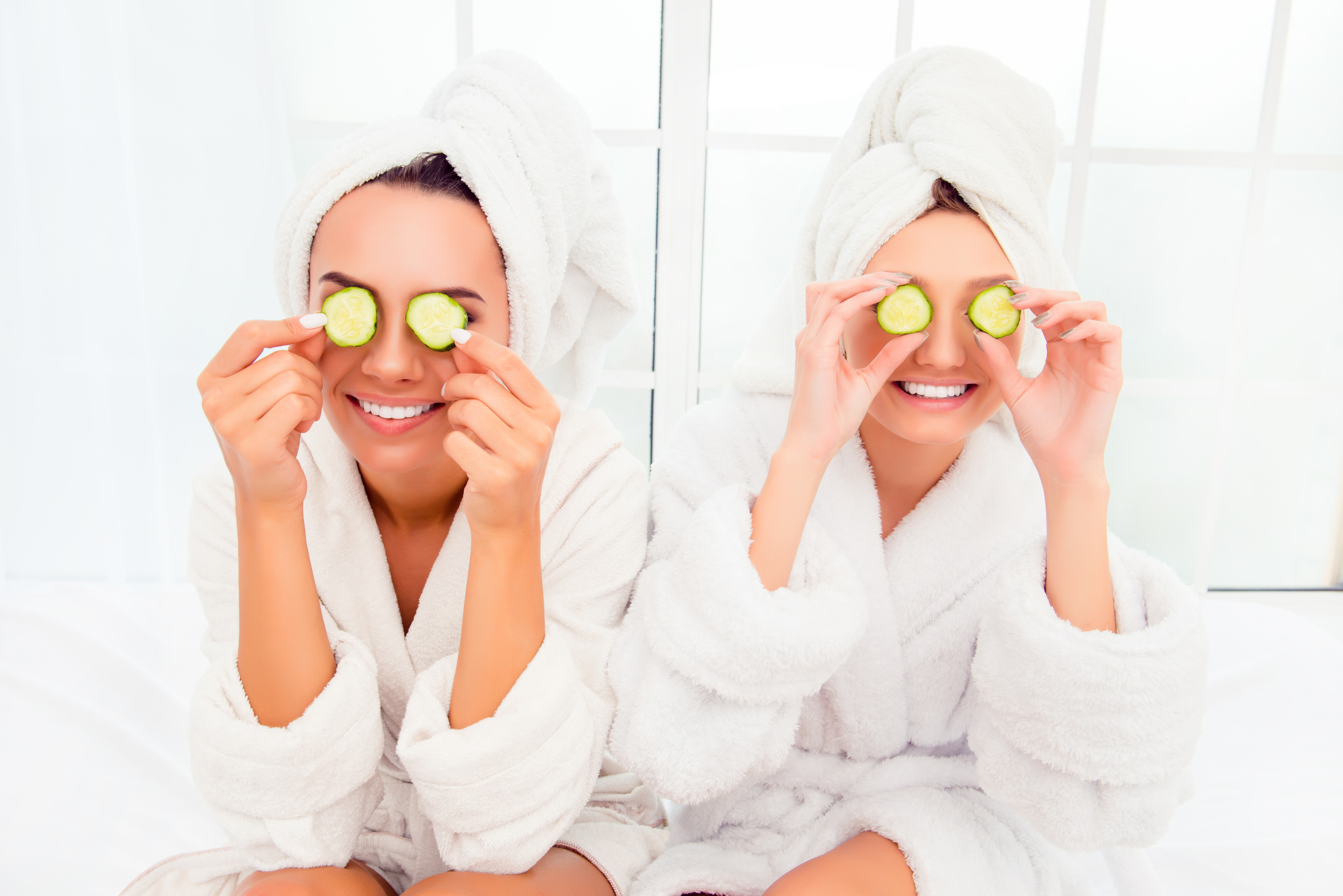 Two pretty women with cucumbers on eyes and towel on their heads