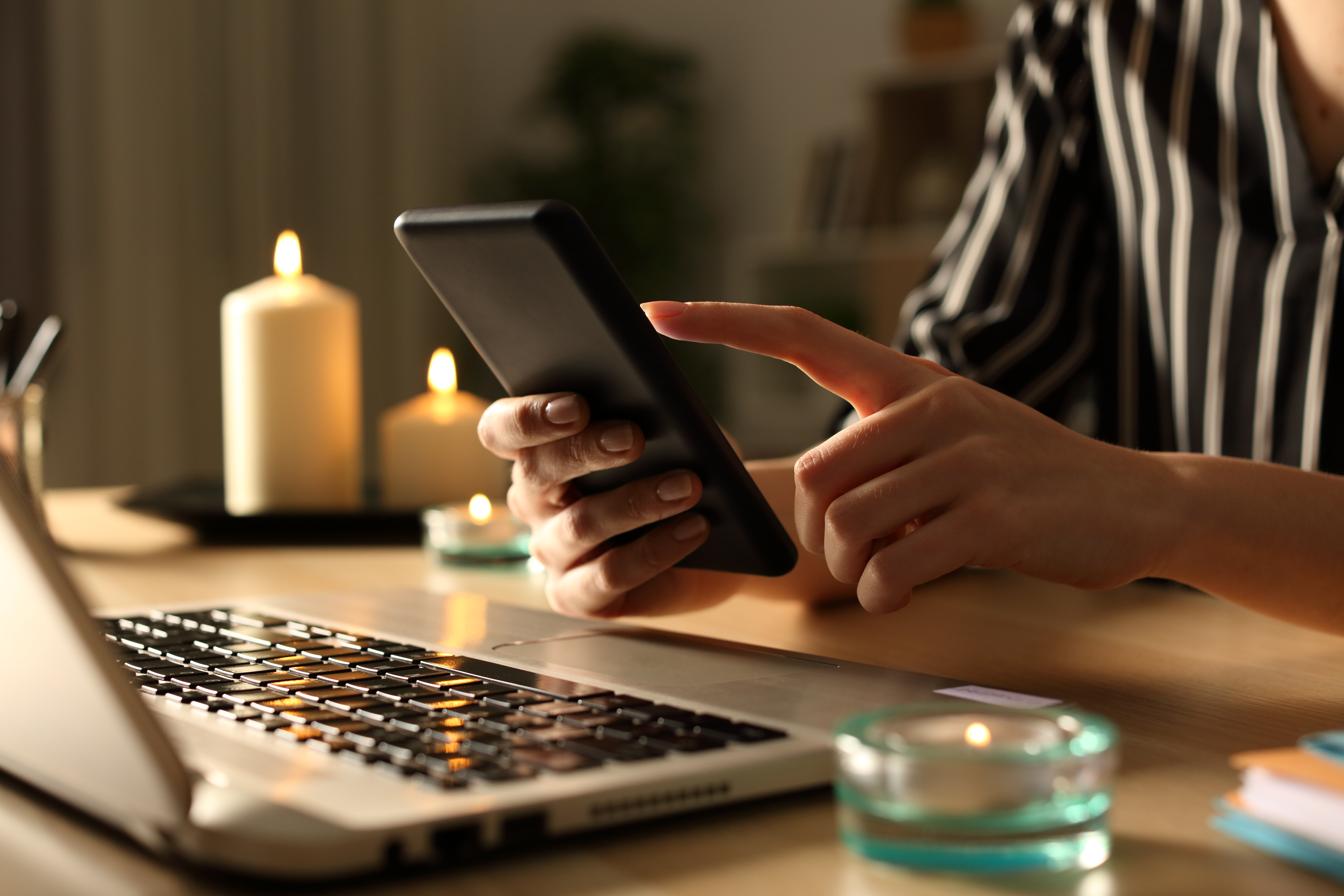 Girl hands using phone on power outage with candles