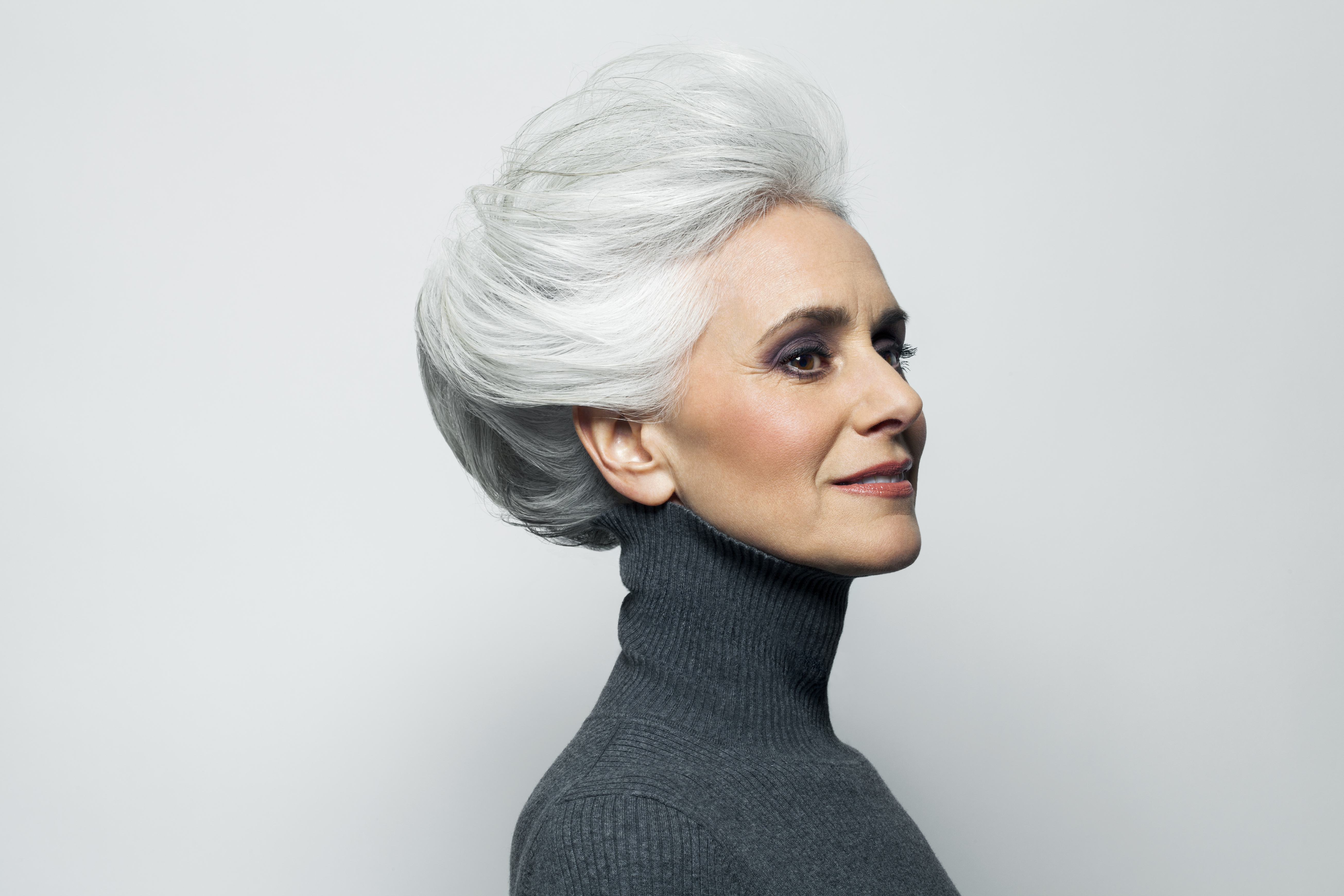 Grey haired woman in grey turtleneck sweater.