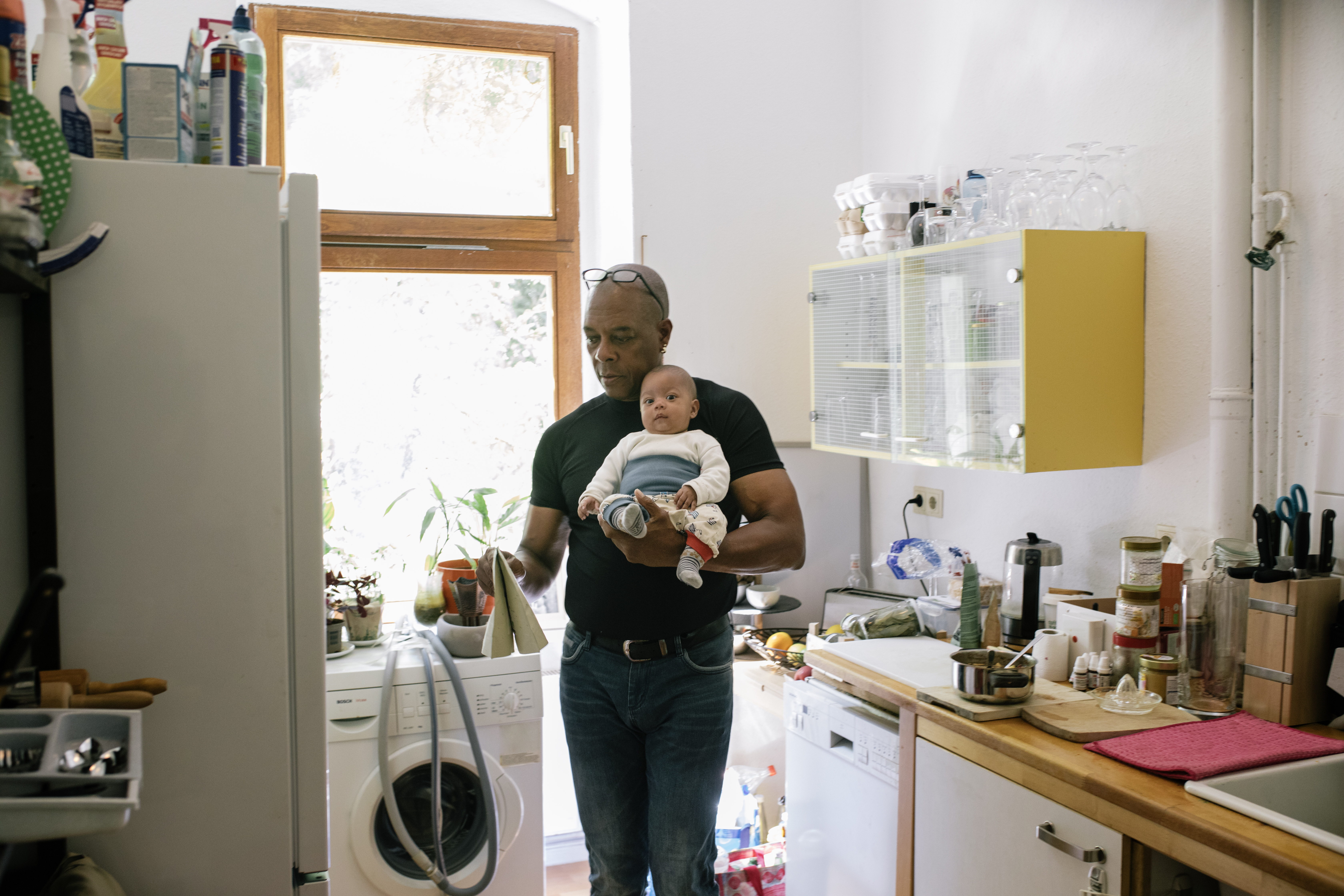 Dad At Home In Kitchen Holding Young Baby