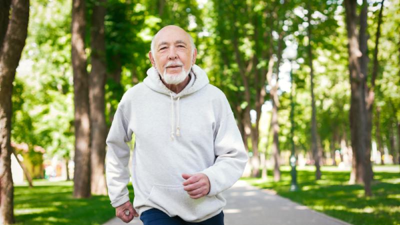 Elderly man running in green park, copy space