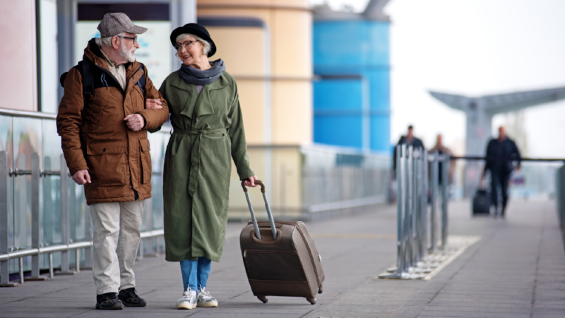 Pleasant senior couple is situating near airport
