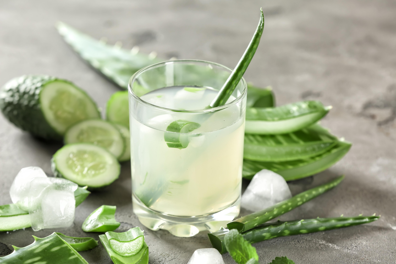 Glass of aloe vera juice on grey table