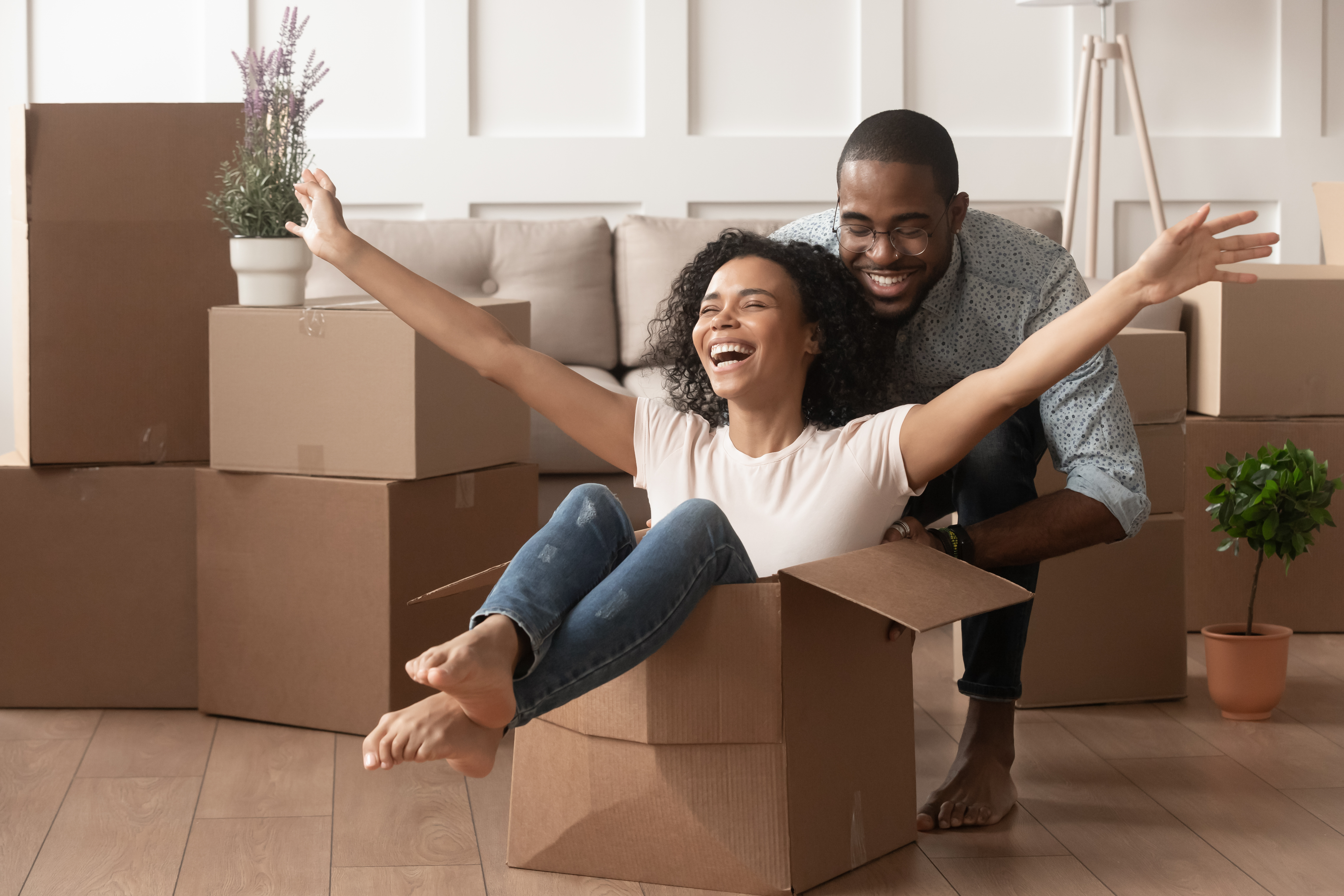 Happy african young couple riding in box on moving day