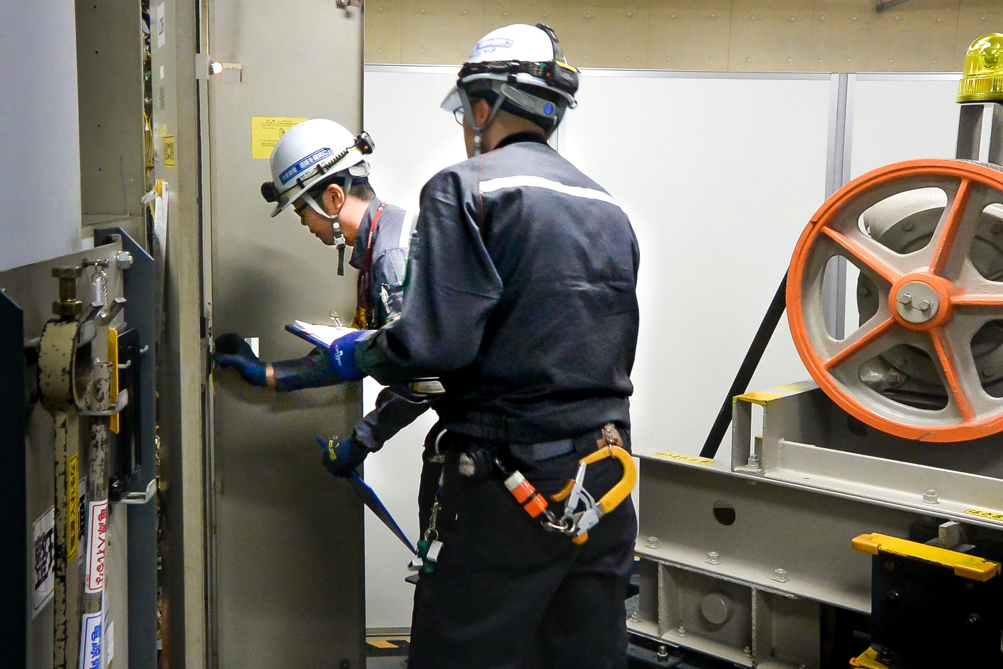 法定検査作業競技中の梅村氏(写真奥)。研修施設内に設置された旧方式のエレベーター実機にて、 制御盤を開き絶縁抵抗を測定中。(撮影時:2017年)