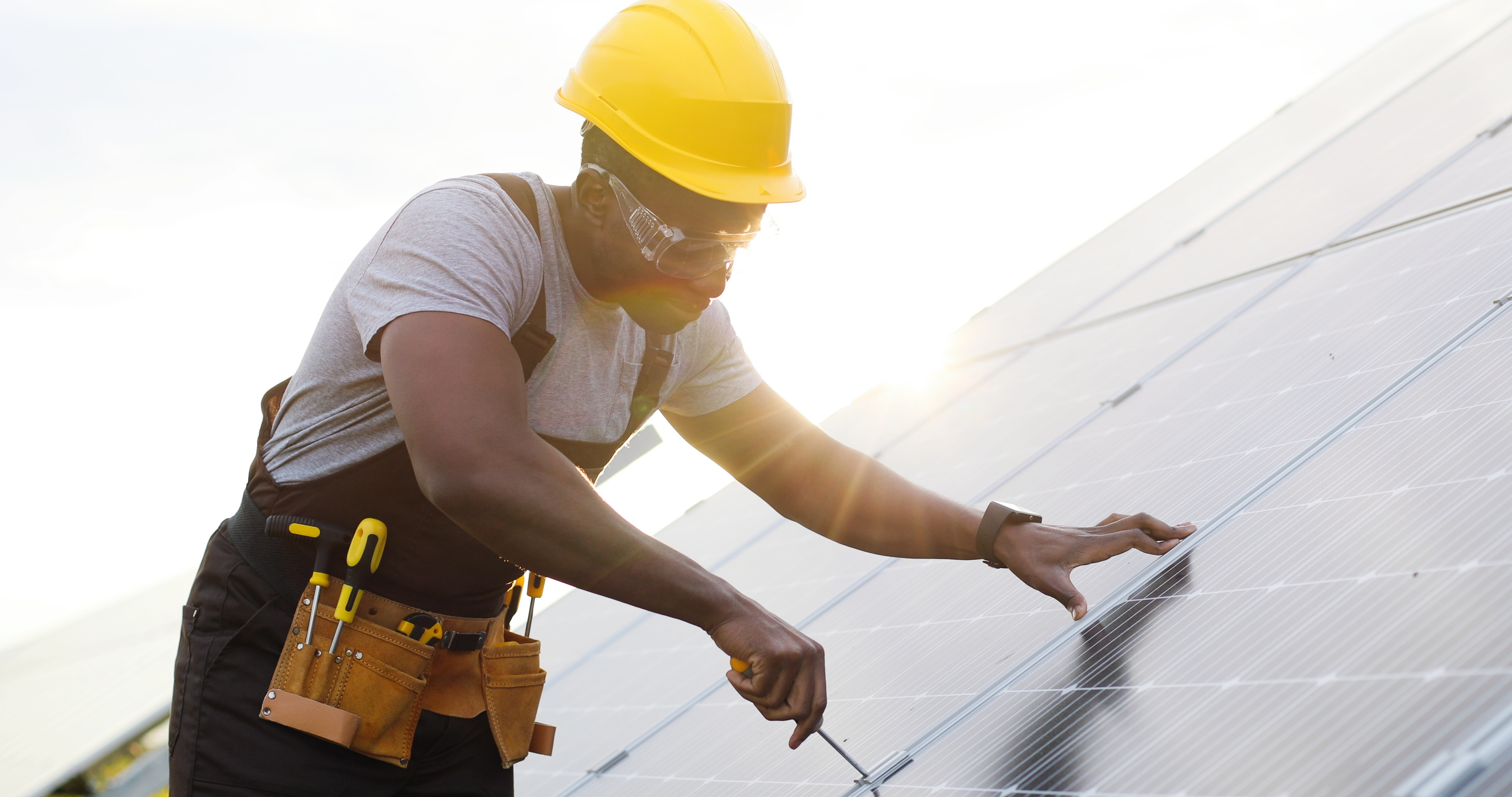 Portrait of african american engineer in safety helmet and uniform at solar power station installing solar panels. Green energy.