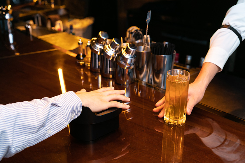 Photo : Payments for drinks and food can be completed merely by placing the palm of one's hand over the device on the bar counter.
