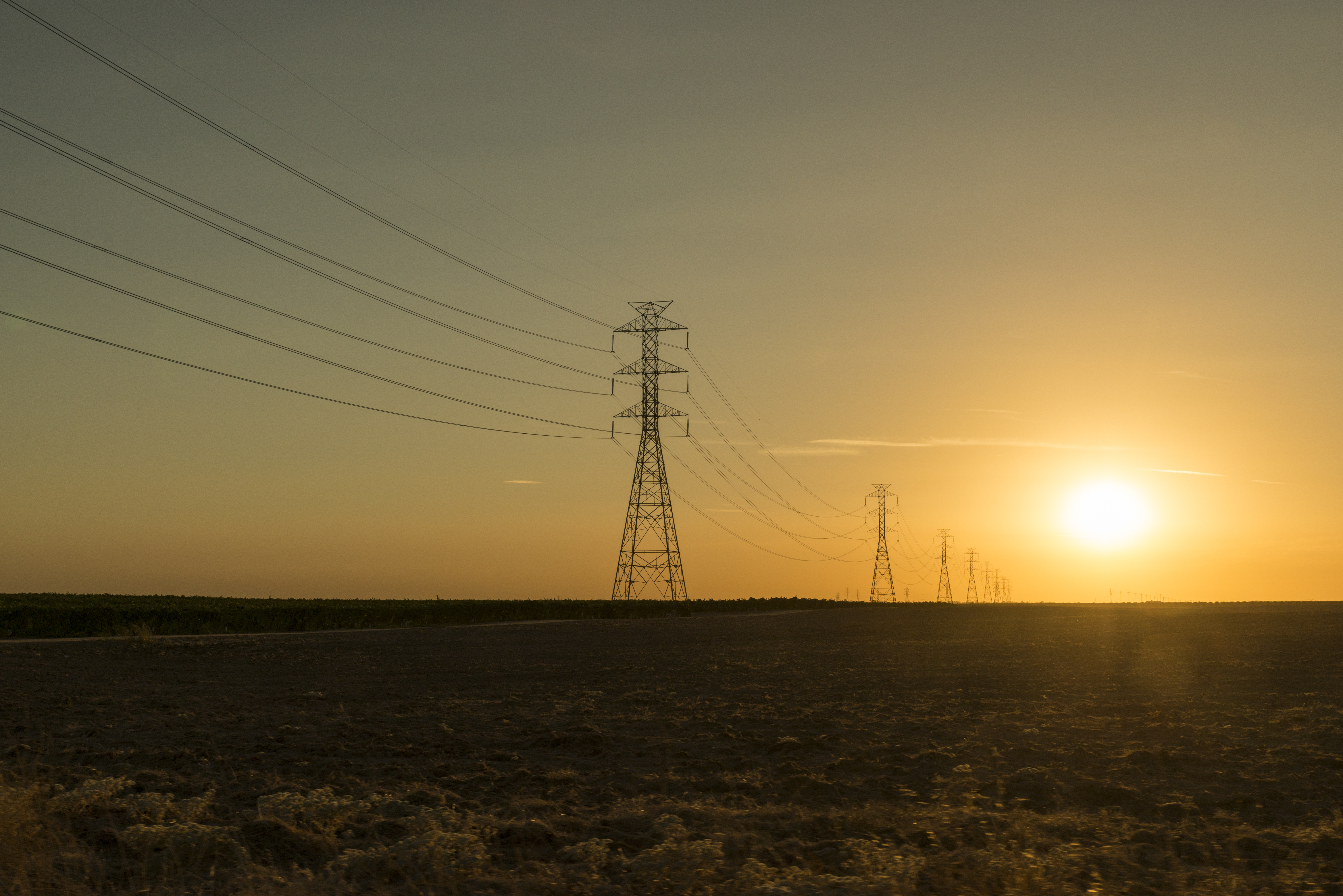 Electrical power transmission lines and pylons on sunset
