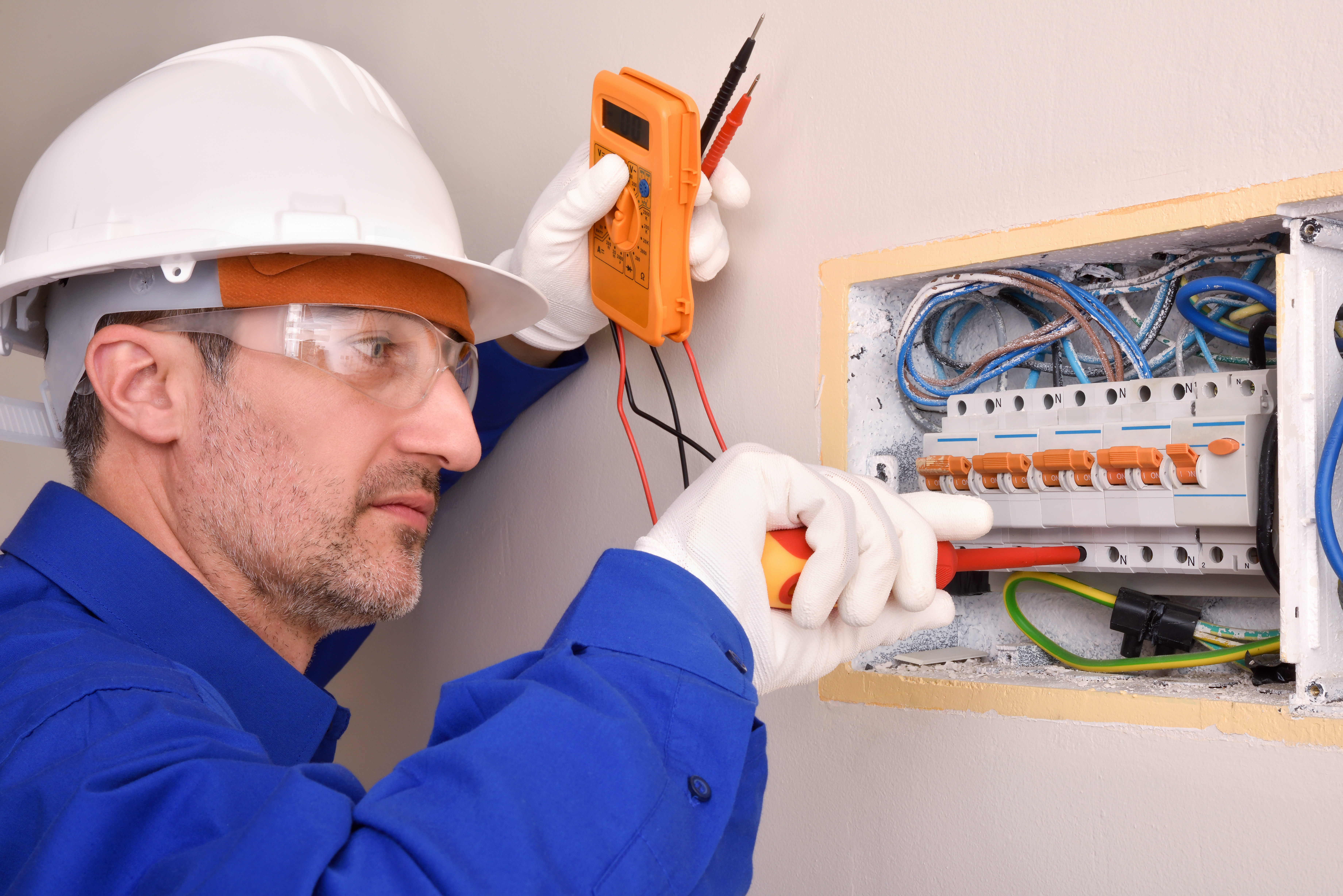 Electrical installer housing working in an electrical panel of house