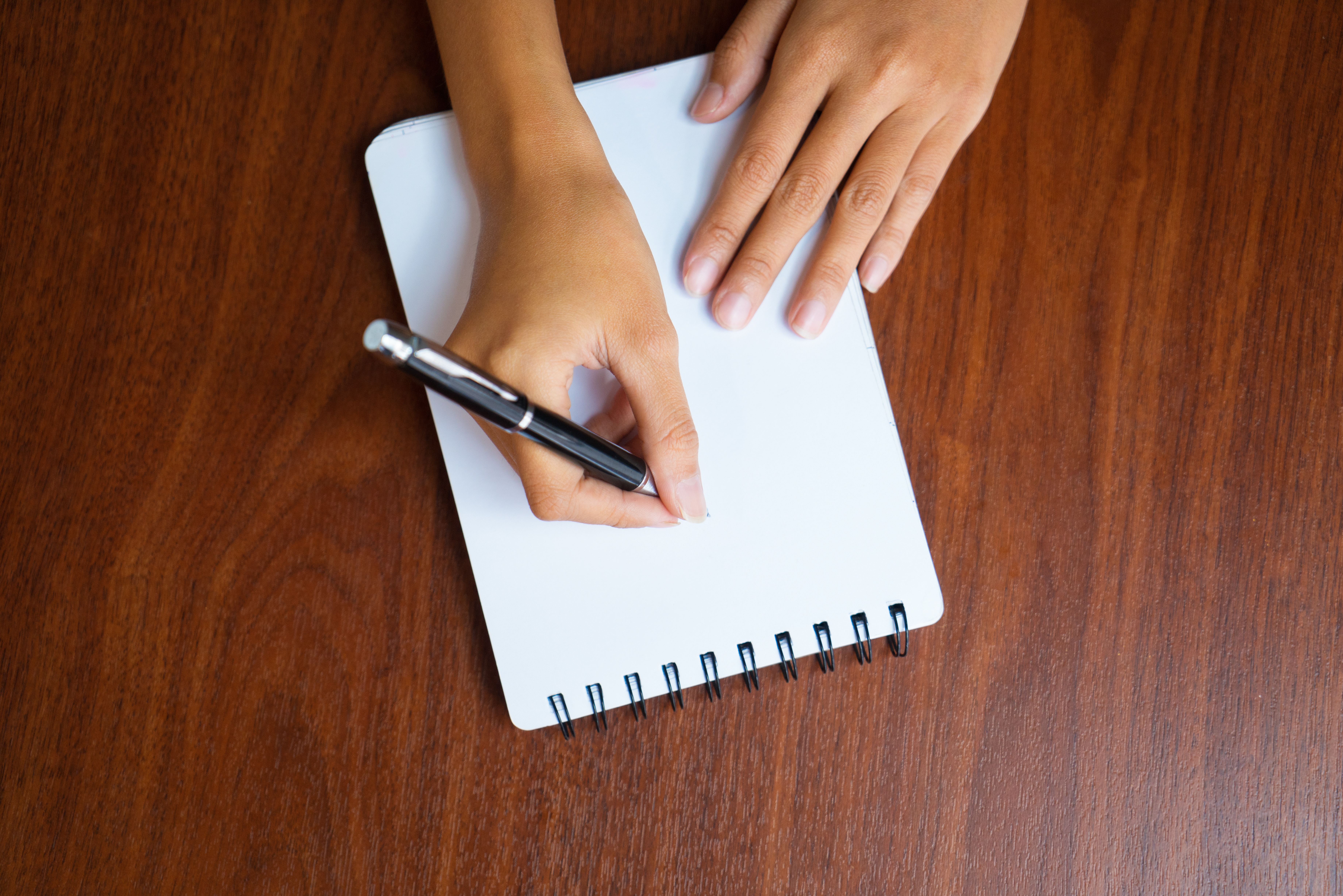 Close-up of hand writing down notes in notepad
