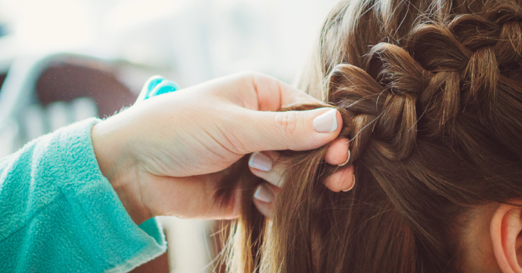 The hairdresser plaits the braid girl. Hands, close-up. Pretty haircut.