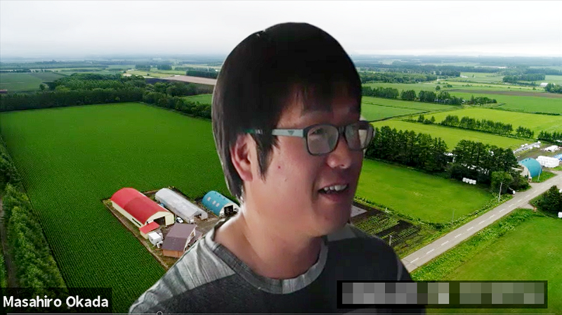 岡田農場の広大な農地をバーチャル背景にして取材に応じる岡田さん