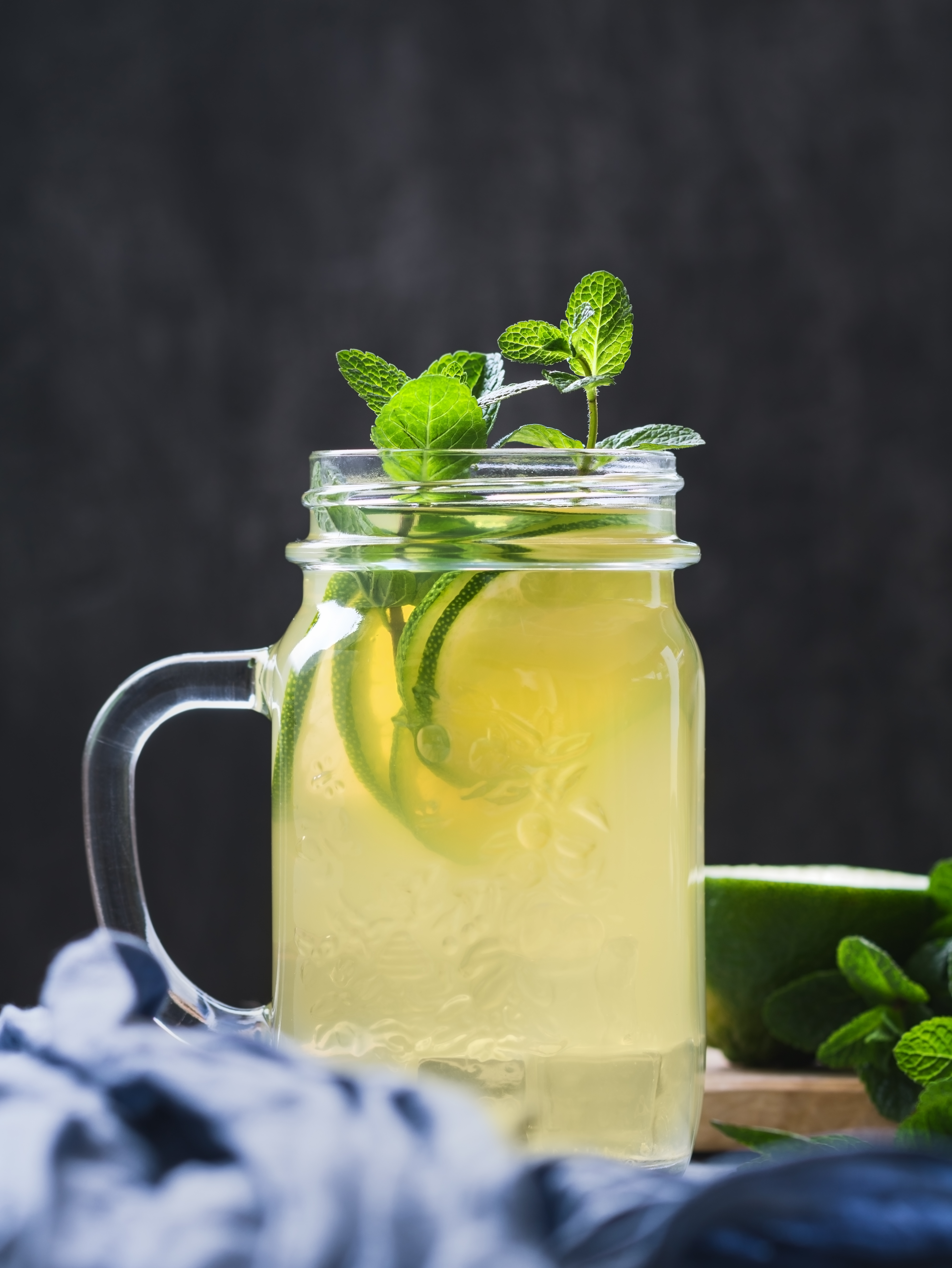 Cold beverage mojito in a glass jar with lime and mint on a table against black wall.