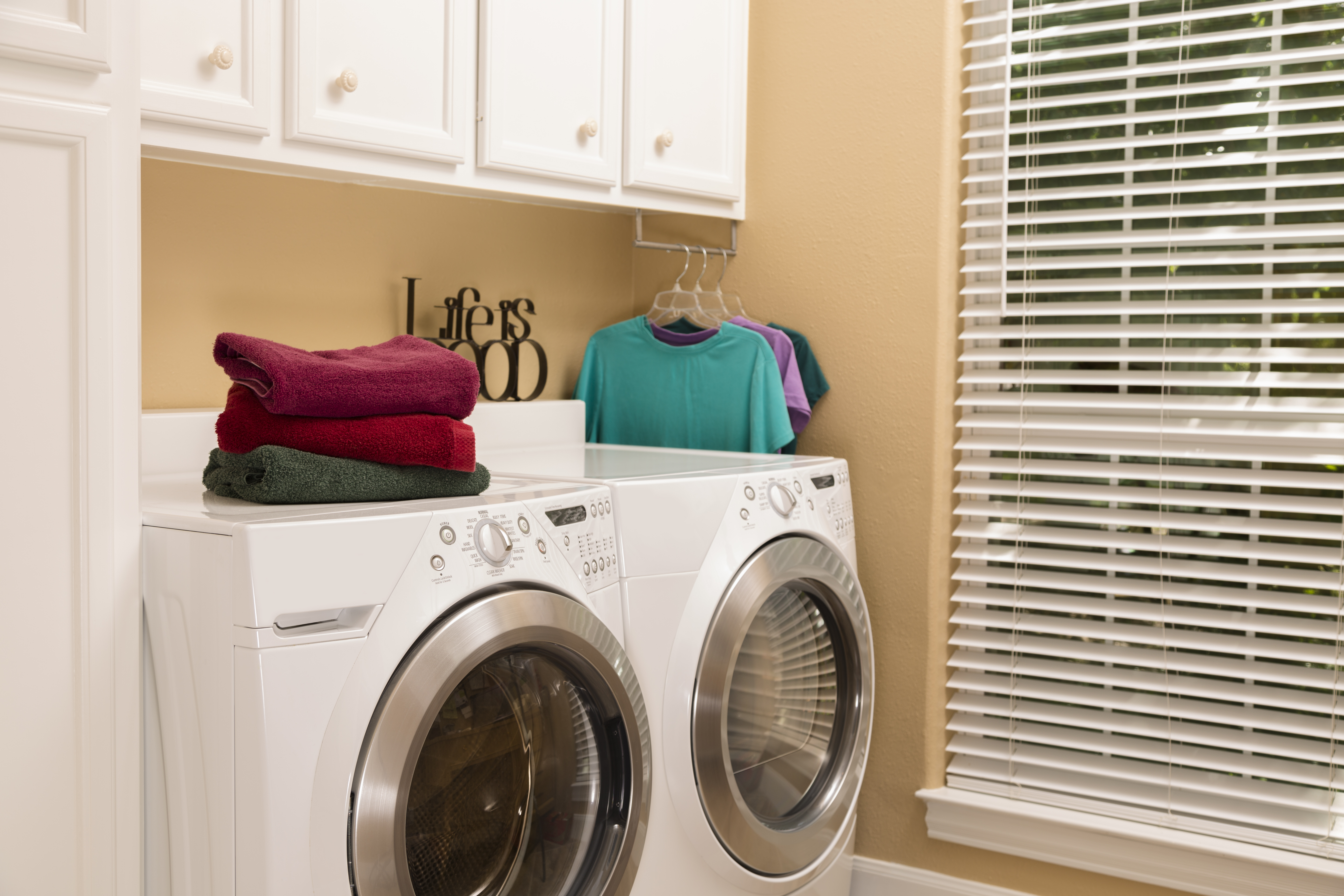 Domestic Life: Laundry room with folded towels, clothes.