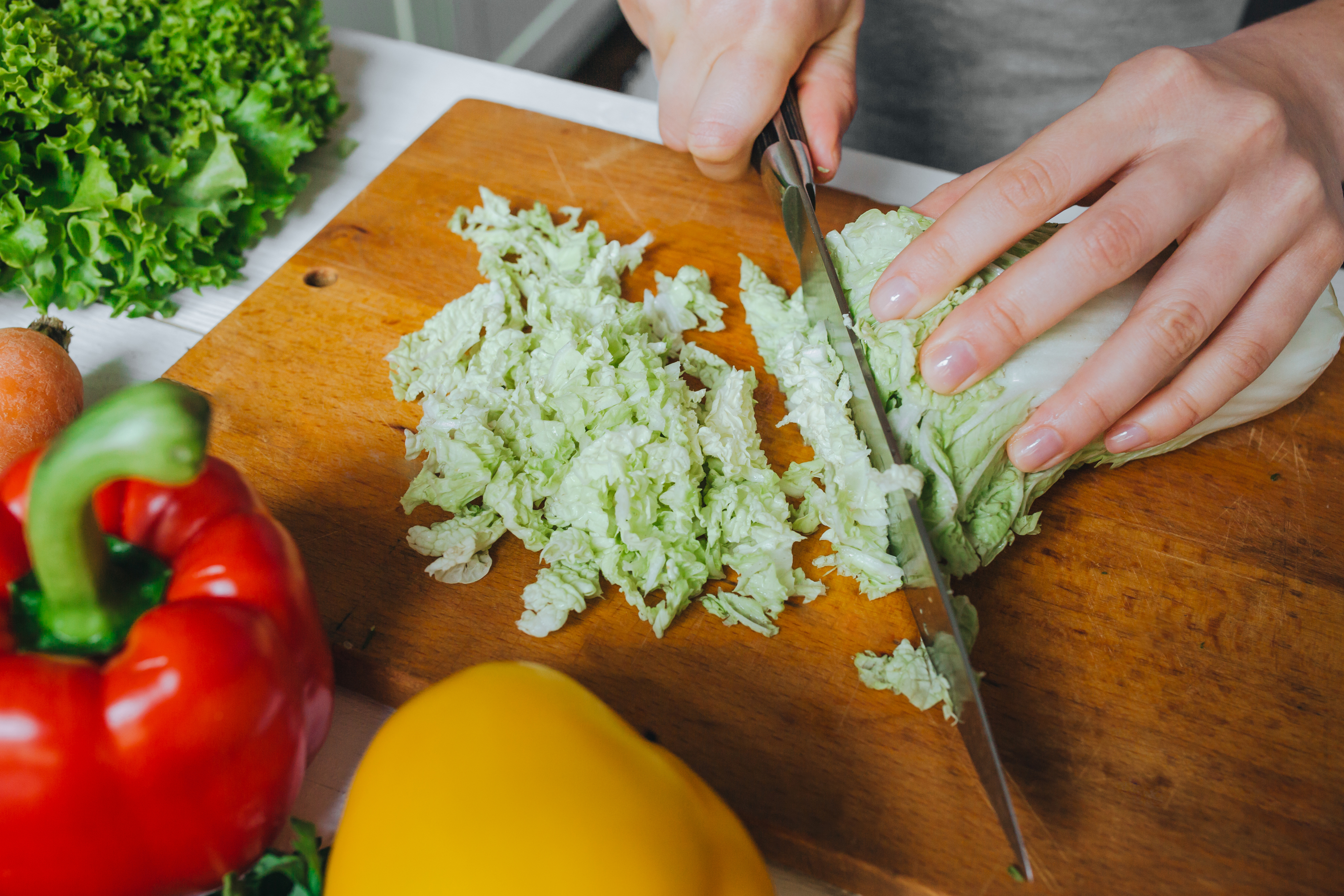 Woman hands cutting fresh green Pekin cabbage on wooden board closeup. White table background. Steel sharp knife reflection.