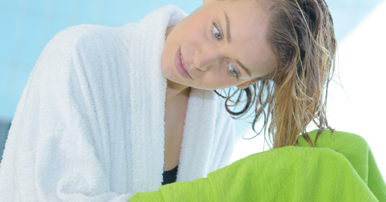 woman drys hairs with towel