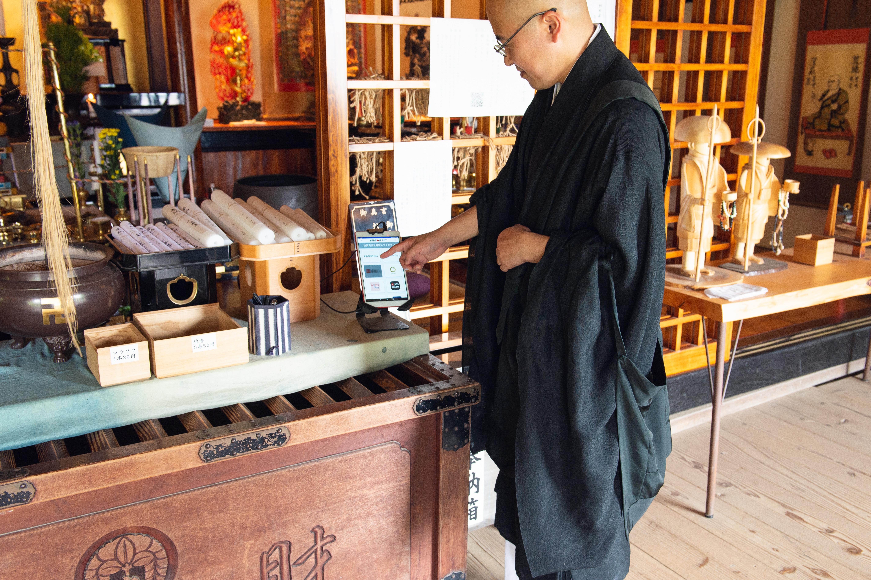 キャッシュレスの決済方法を説明する平等寺住職の谷口氏