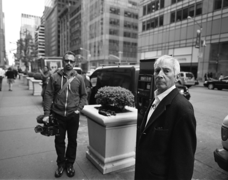 "Robert Durst wearing a suit standing next to ""The Jinx"" director Andrew Jarecki on 6th Avenue in New York City"