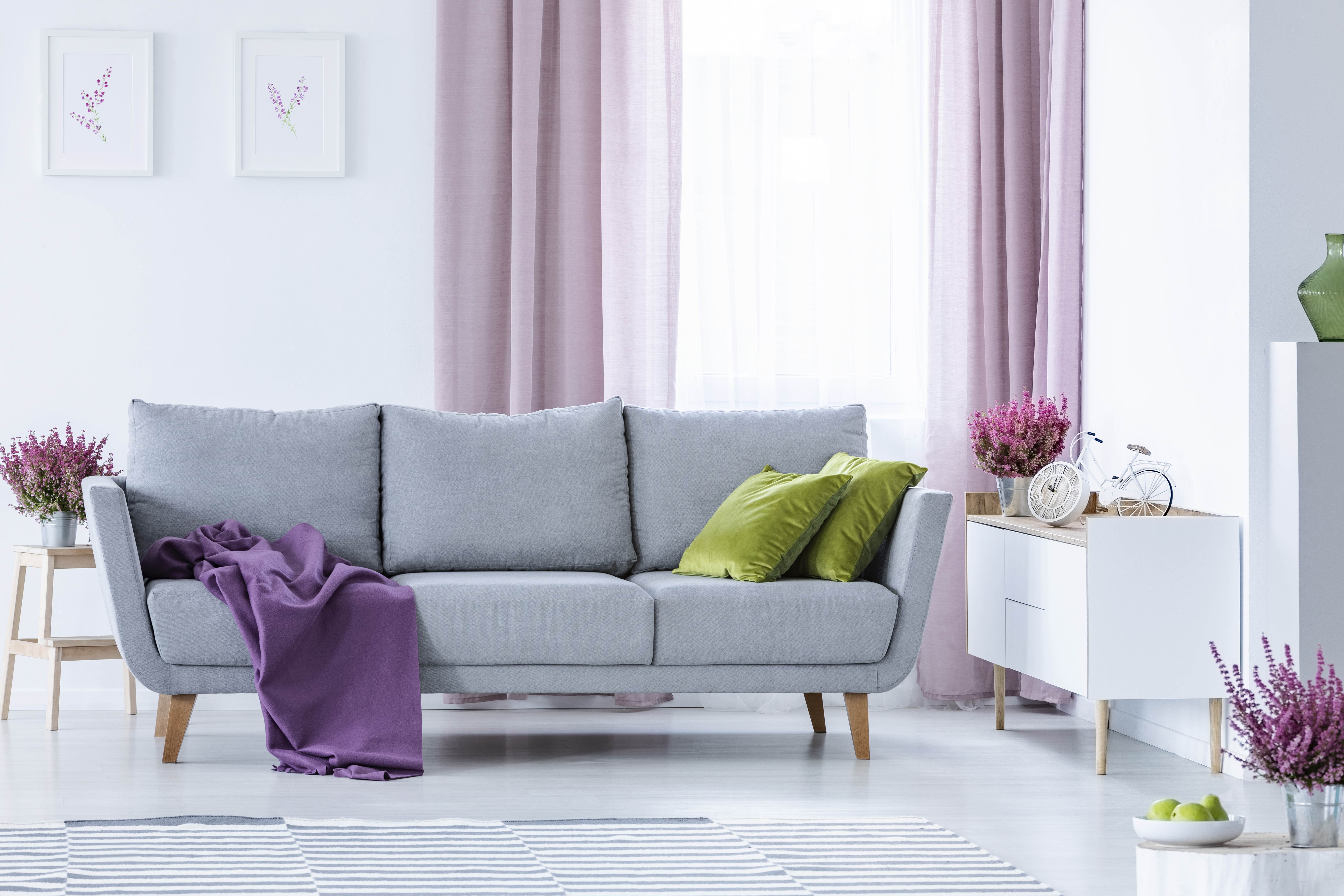 Elegant living room with big comfortable grey couch with olive green pillows and violet blanket in the middle of stylish living room with heater in pots and lilac curtainsbike