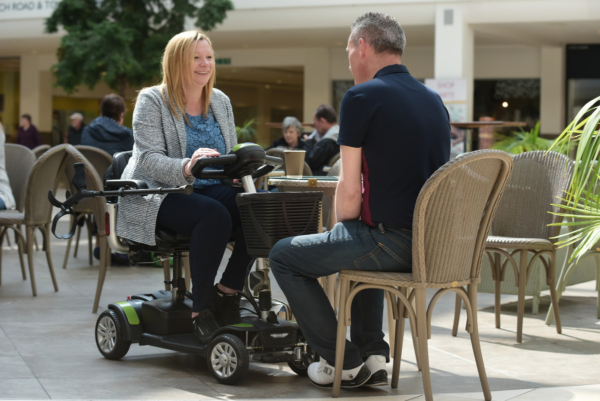 Couple chatting in cafe with mobility scooter.jpg