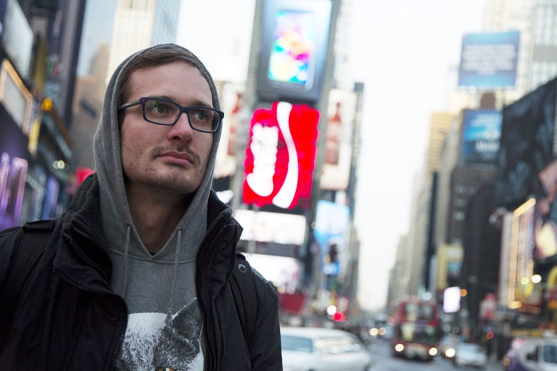 "David Farrier, Director of HBO&squot;s ""Tickled"" stands in Times Square wearing a hooded sweatshirt"