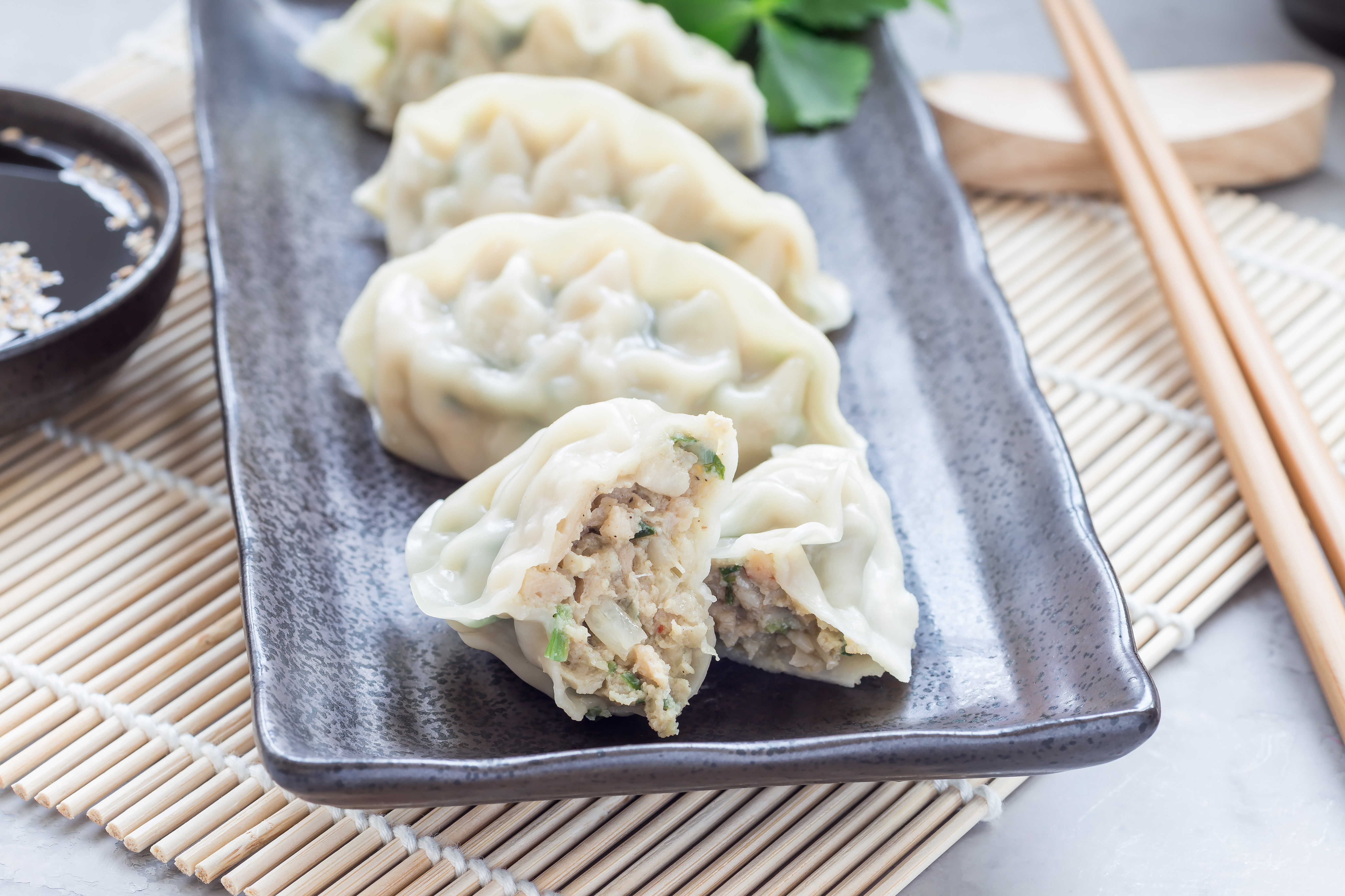 Steamed Korean dumplings Mandu with chicken meat and vegetables on a black plate, horizontal
