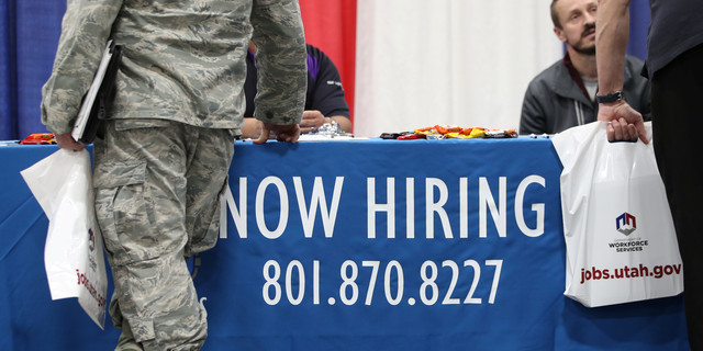 Veterans and military personnel discuss job opportunities at a military job fair in Sandy, Utah
