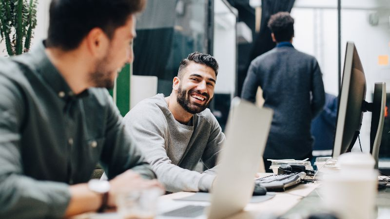 Smiling colleagues looking at each other while sitting by desk in office