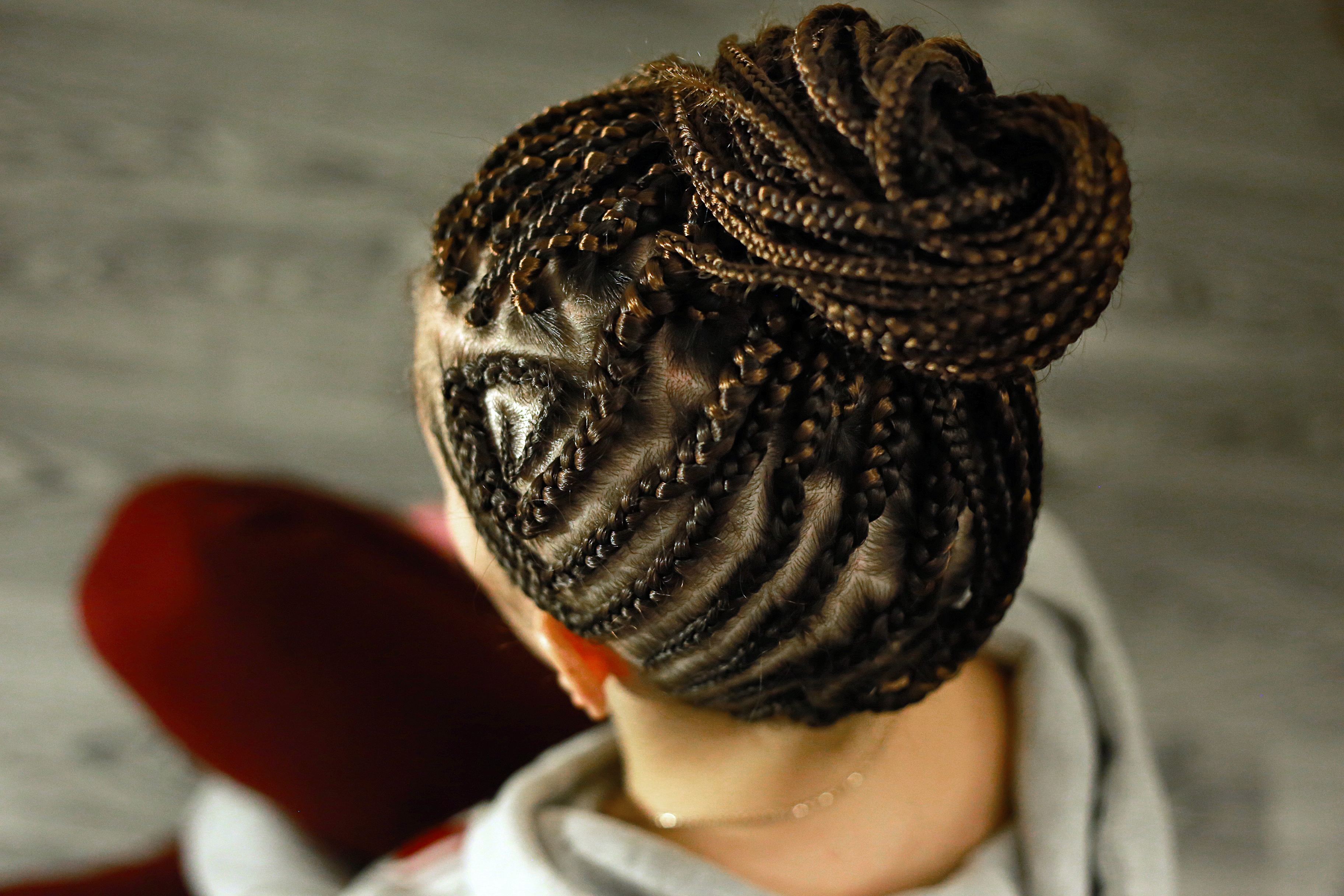 African braids are gathered in the tail with a pattern from the cornrow on the temple, an original youth hairstyle