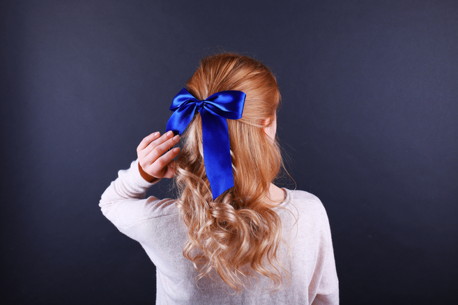 the back of the head of a red-headed woman with a big blue bow