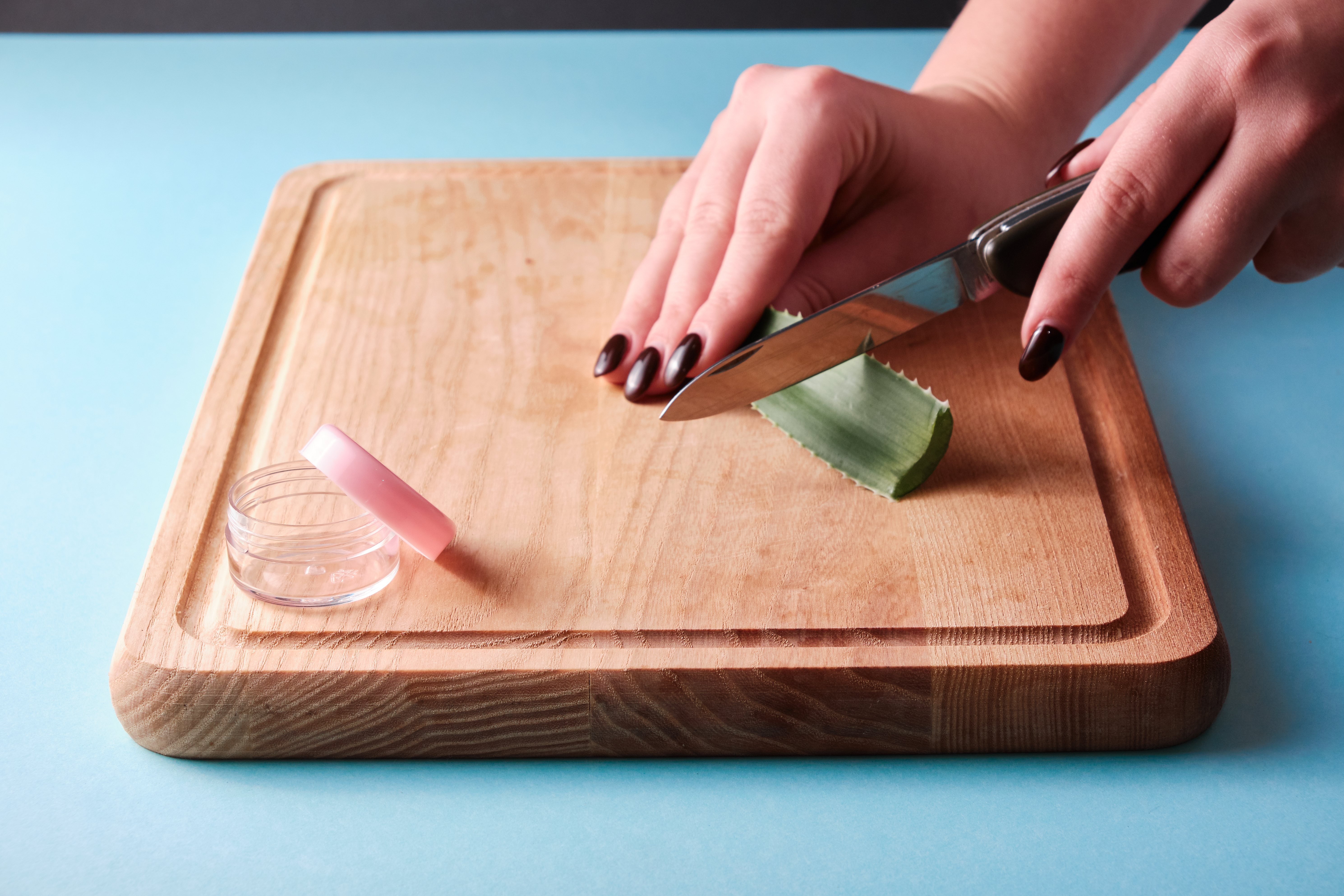 Cutting aloe vera slices with a knife next to a open empty box with pink cap, blue background