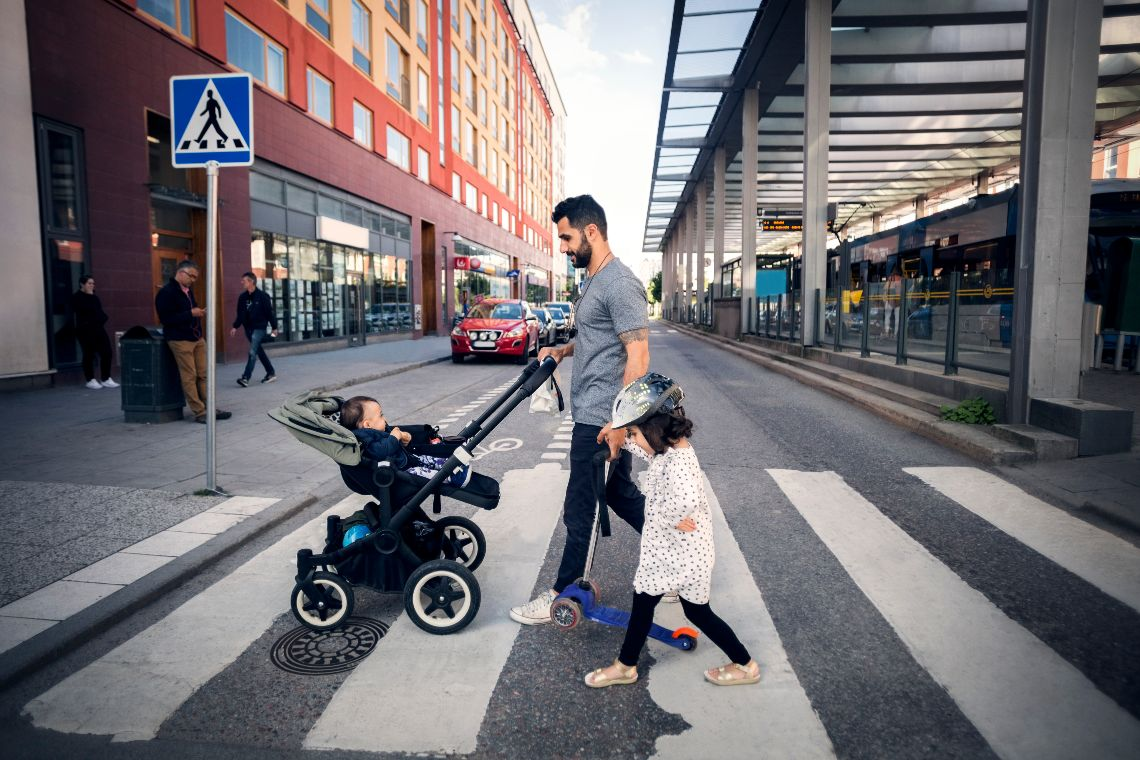 Side view of father crossing street with daughter while holding baby stroller in city