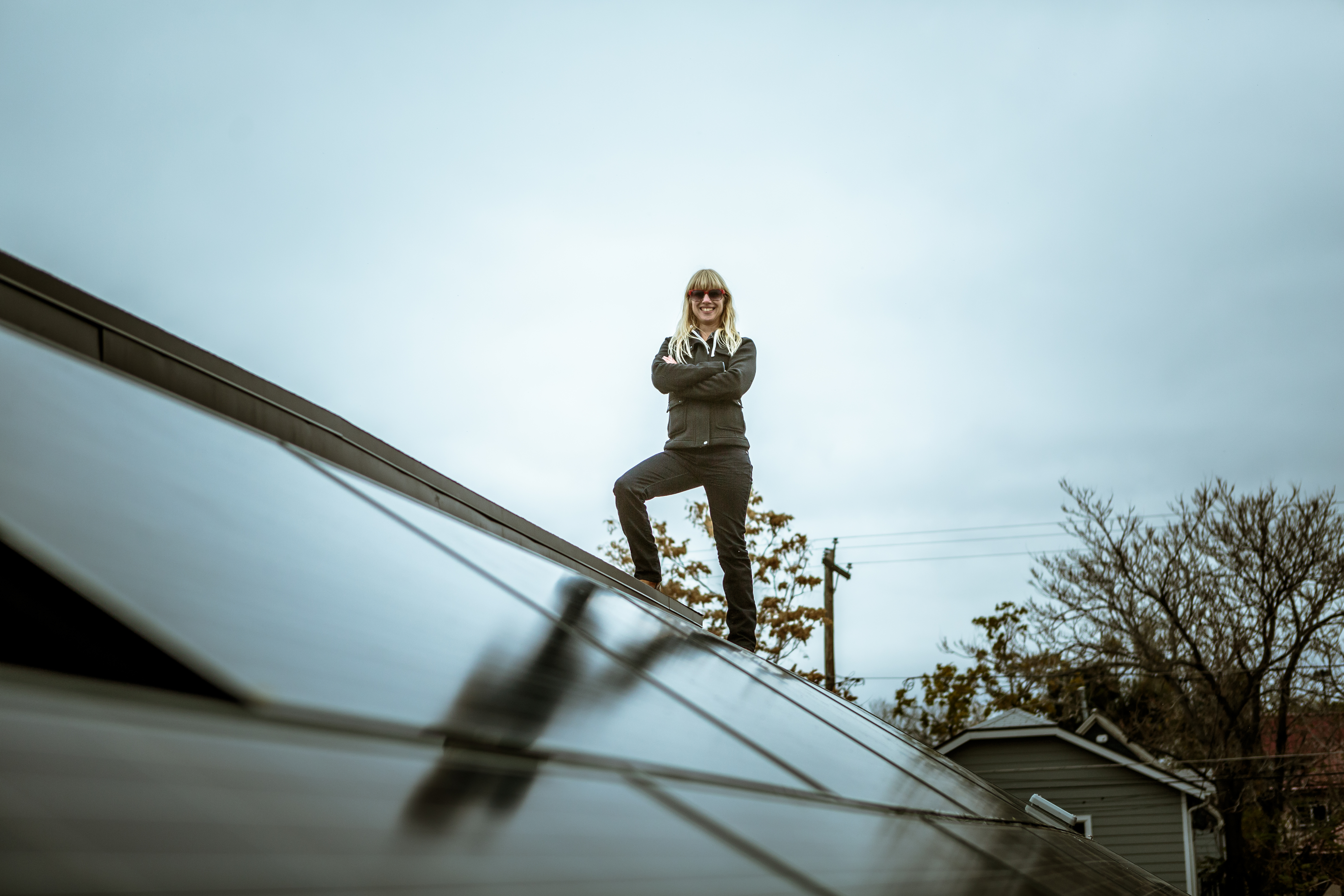 Portrait of mid adult woman standing on newly solar paneled house roof